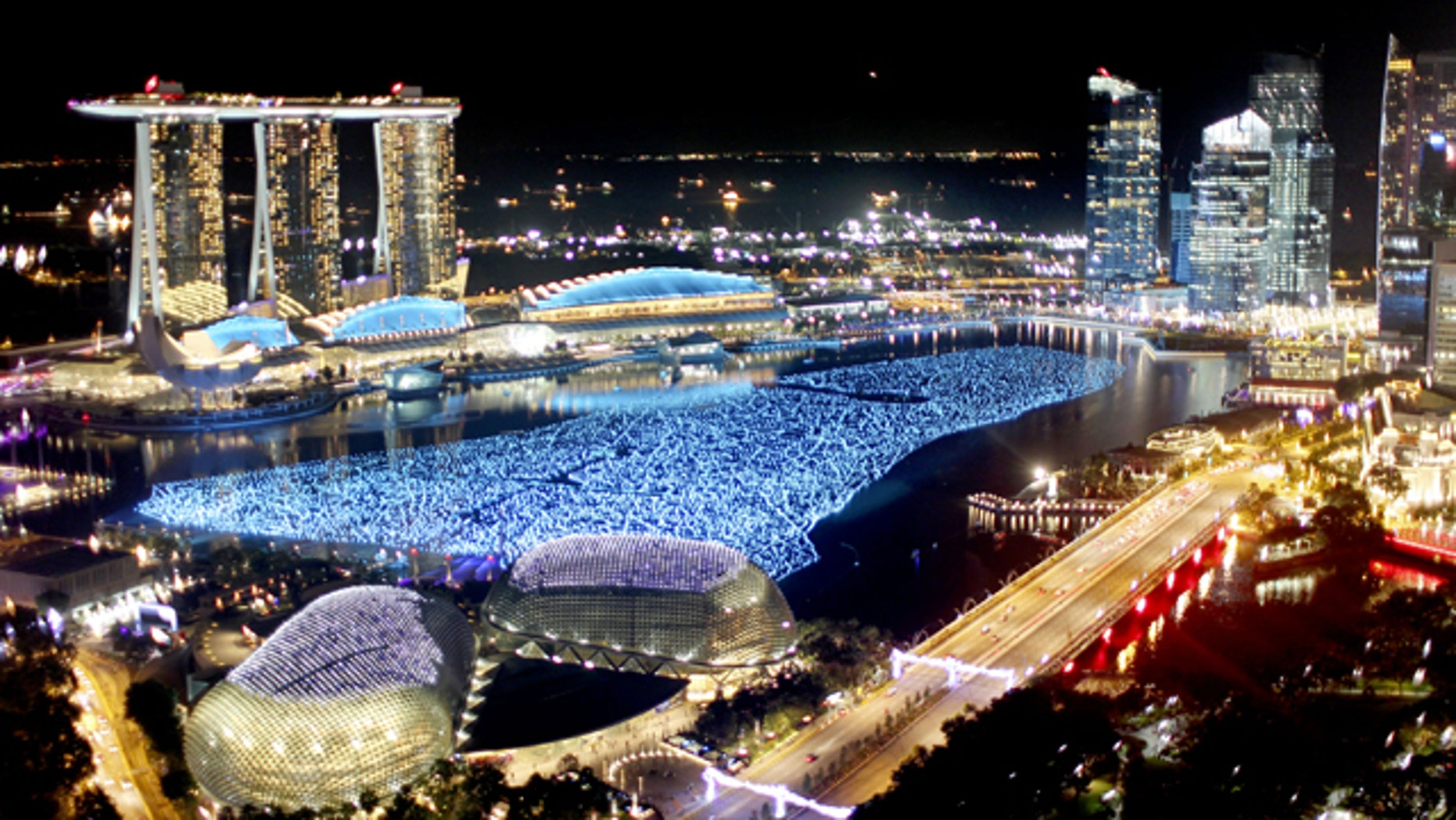 In this photo taken on Friday, Dec. 31, 2010, the financial skyline is lit while the newly opened Marina Bay Sands casinos, left, tower over the bay area as they await New Year's day countdown.