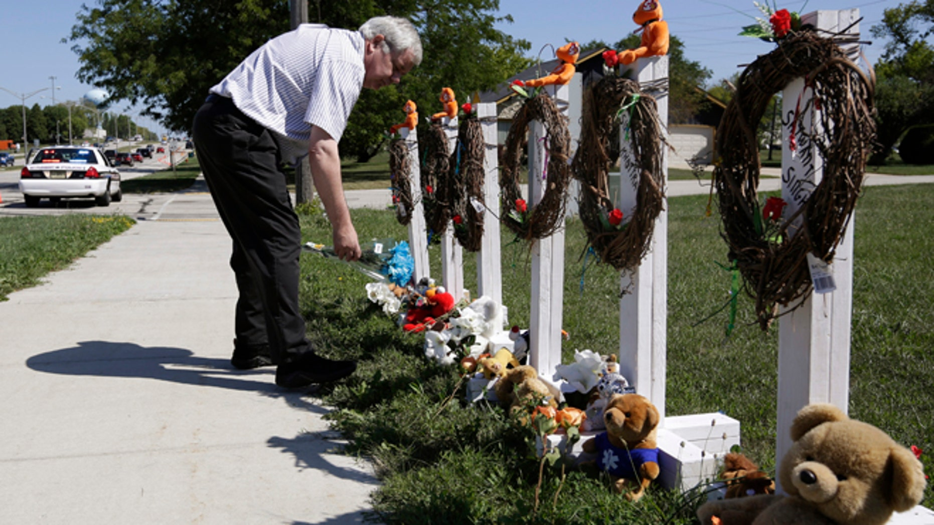 August 7, 2012: Peter Gallagher leaves flowers at a memorial honouring the six victims of a shooting at a Sikh Temple in Oak Creek, Wisconsin.