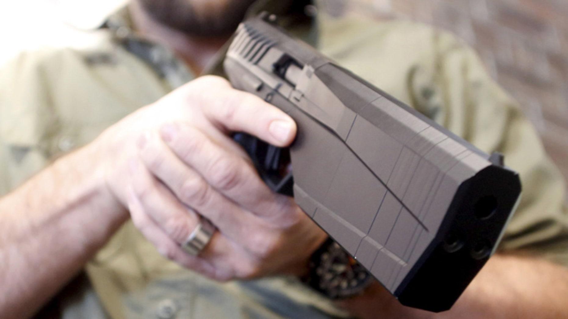 FILE: Feb. 23, 2016: SilencerCo CEO Joshua Waldron cradles a handgun with a built-in suppressor. West Valley City, Utah. (Reuters)