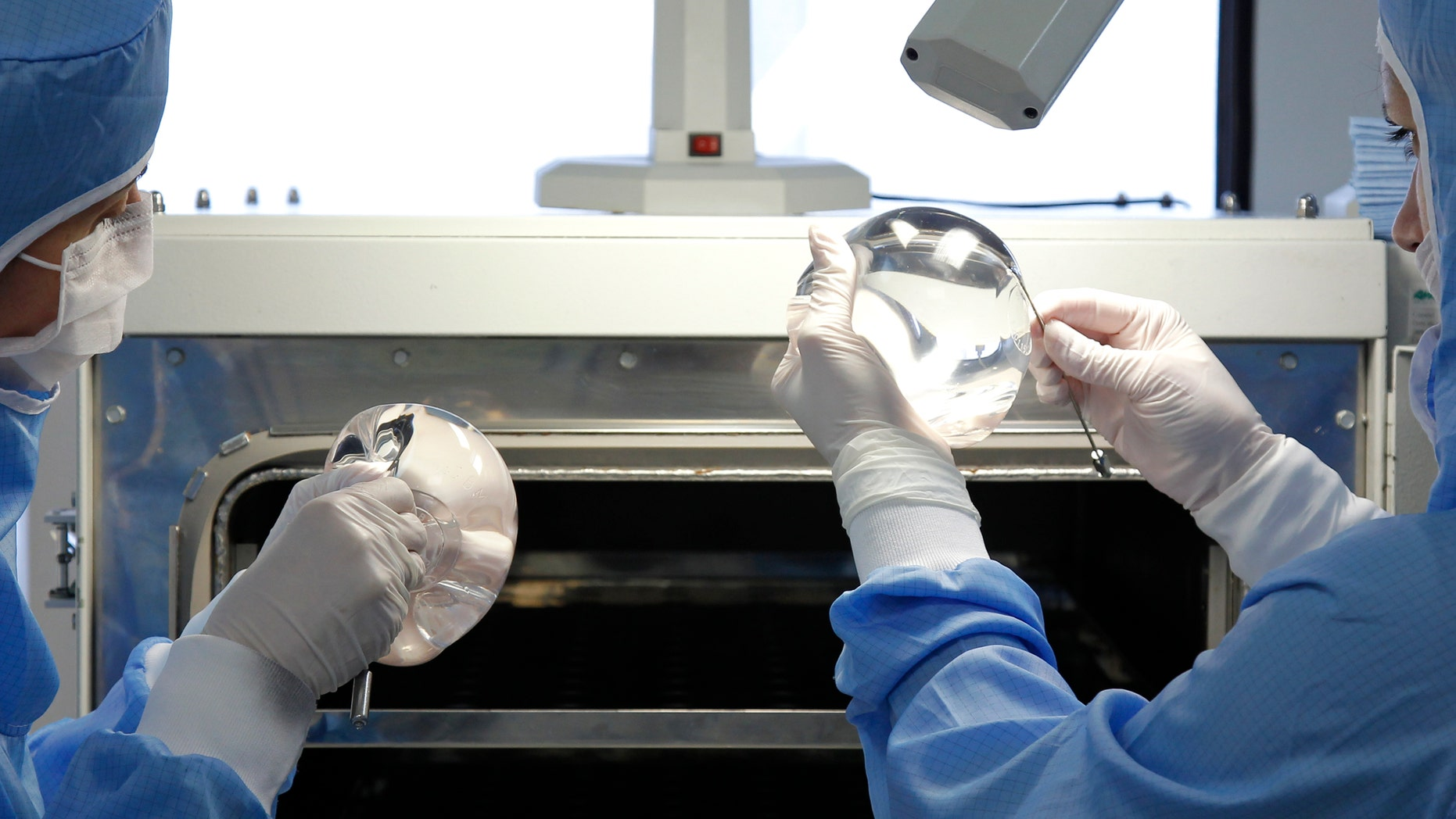 Technicians work in the processing of silicone gel breast implant manufactured by the French company Sebbin laboratories in Boissy-l'Aillerie, northern Paris January 12, 2012. REUTERS/Benoit Tessier