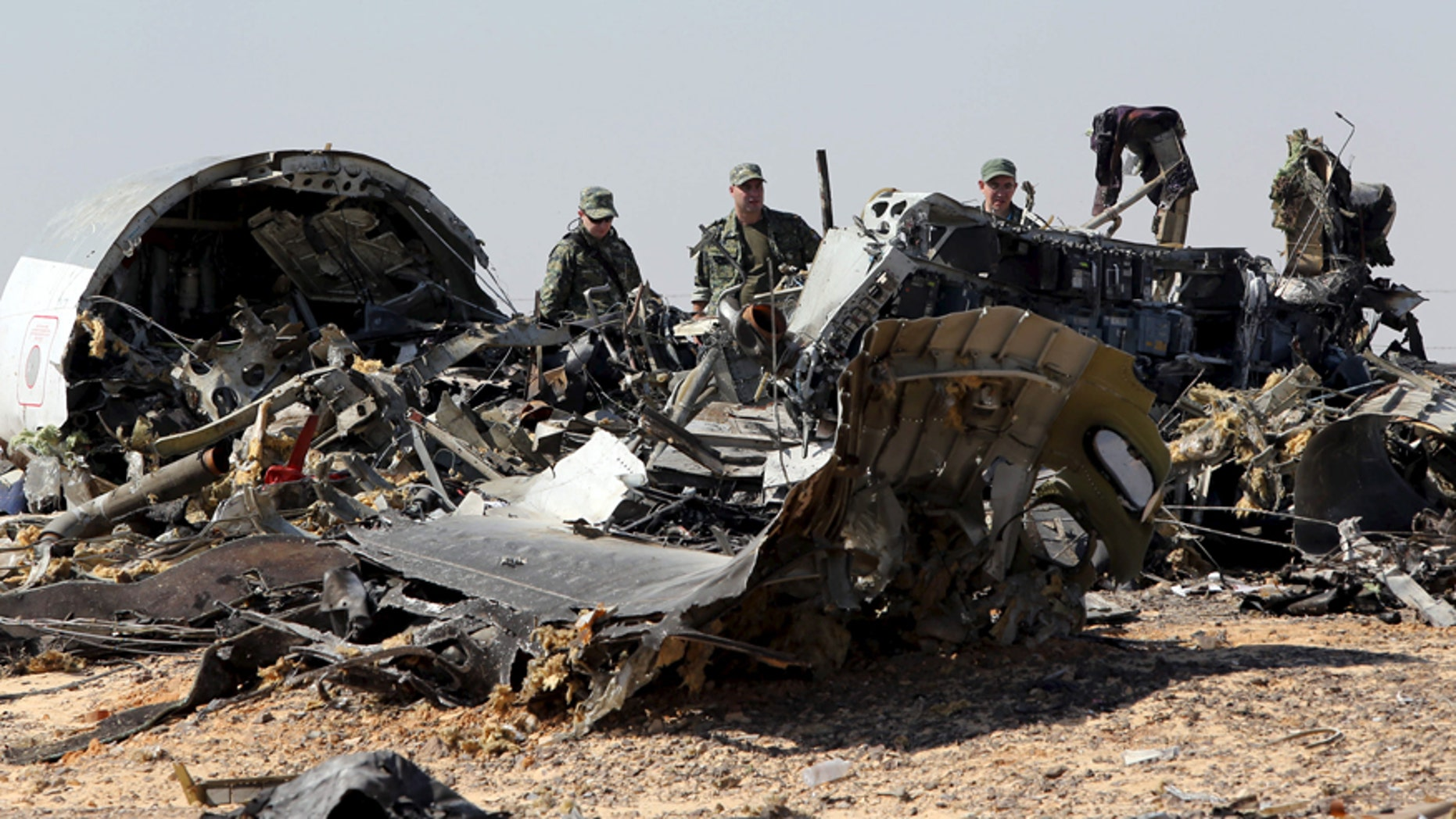 Nov. 1, 2015: Military investigators from Russia stand near the debris of a Russian airliner at the site of its crash at the Hassana area in Arish city, north Egypt.