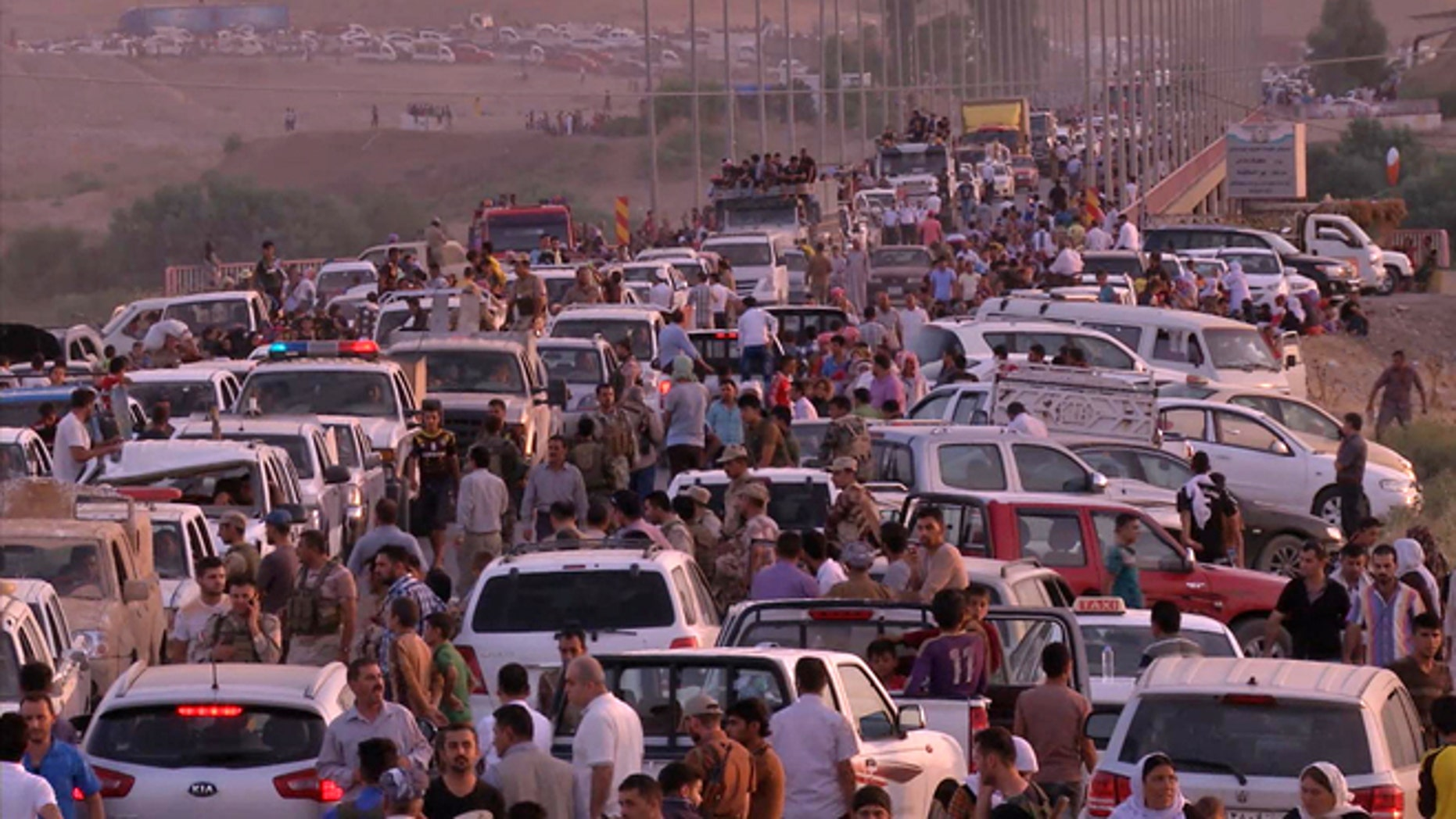 This image made from video taken on Aug. 3, 2014 shows Iraqi people from the Yazidi community arriving in Irbil in northern Iraq after Islamic militants attacked the towns of Sinjar and Zunmar.