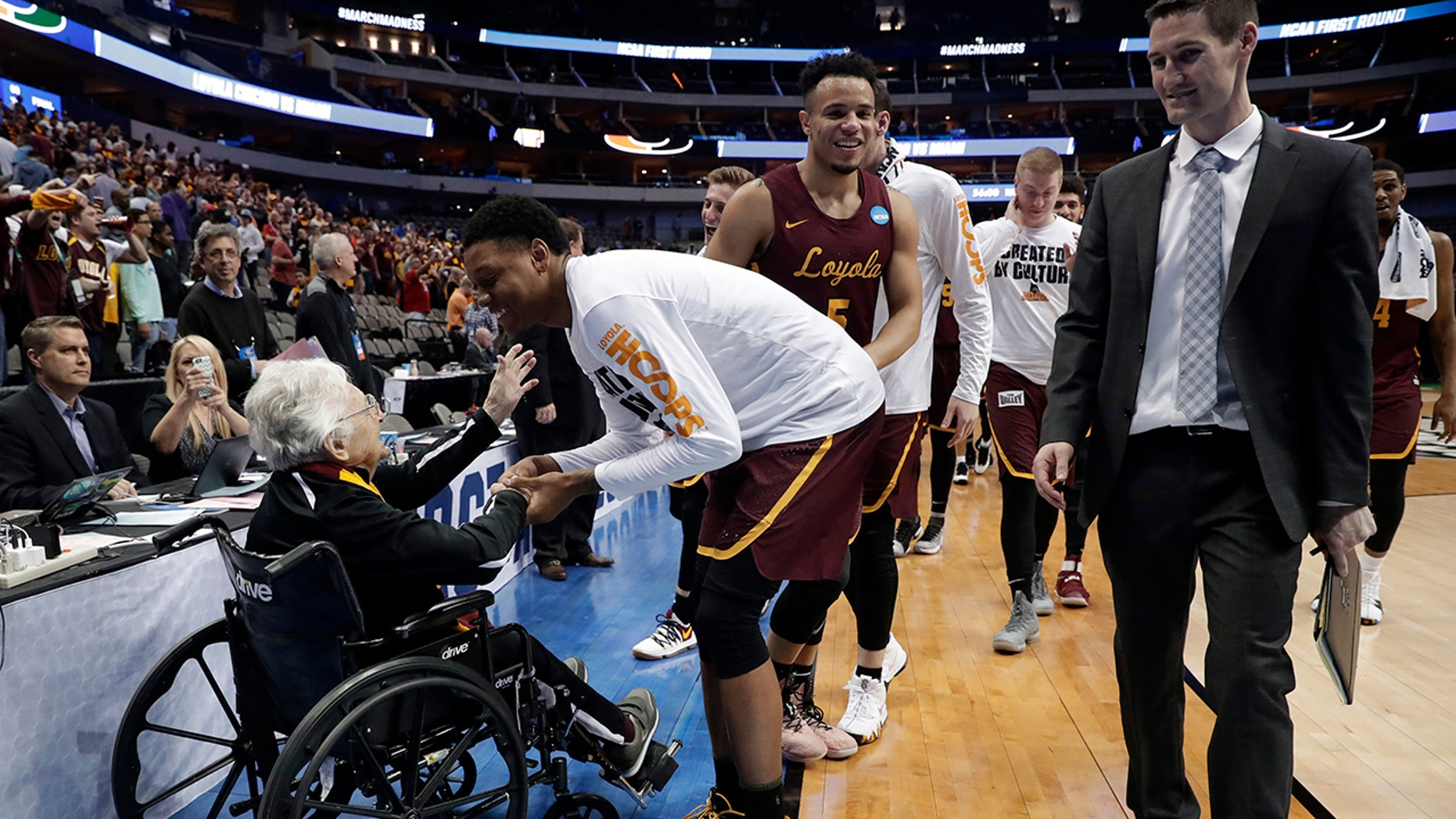 Sister Jean Dolores Schmidt, left, greets the Loyola-Chicago basketball team as they walk off the court after their win over Miami in a first-round game at the NCAA college basketball tournament in Dallas, March 15, 2018.