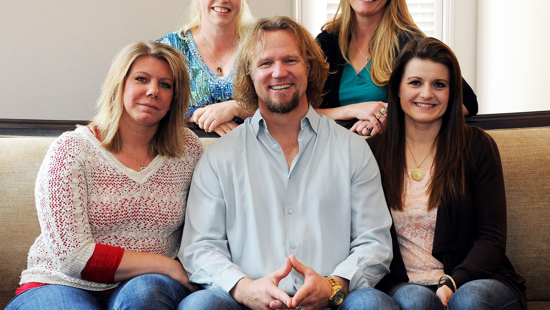 July 10, 2013. Kody Brown poses with his wives at one of their homes in Las Vegas.
