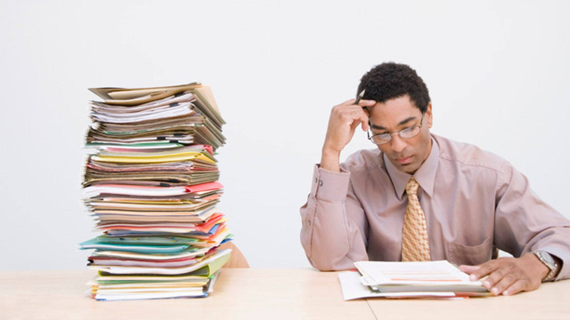 Businessman sitting next to stack of documents on desk, clocks on wall