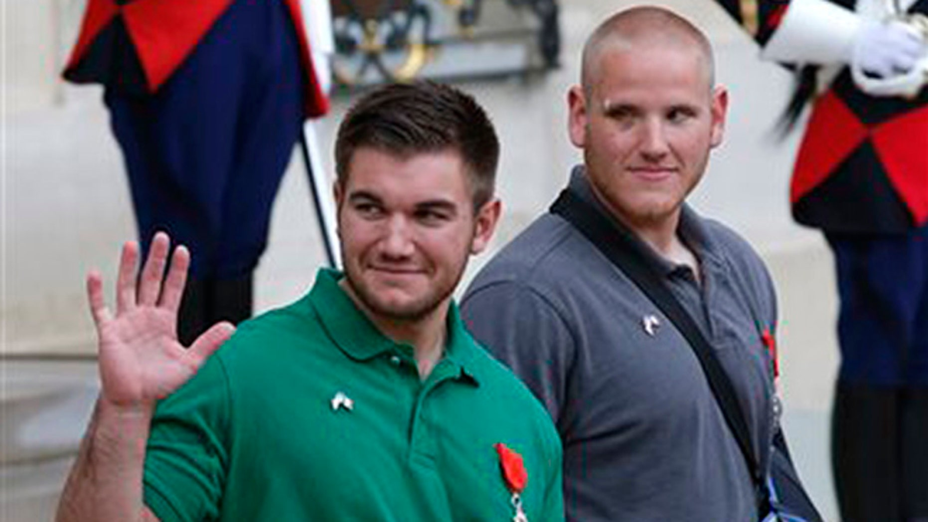 U.S. National Guardsman from Roseburg, Oregon, Alek Skarlatos , left, waves to the media as he leaves the Elysee Place in Paris, France, with U.S. Airman Spencer Stone, after being awarded with the French Legion of Honor by French President, Francois Hollande, Monday, Aug. 24, 2015. (AP Photo/Michel Euler)
