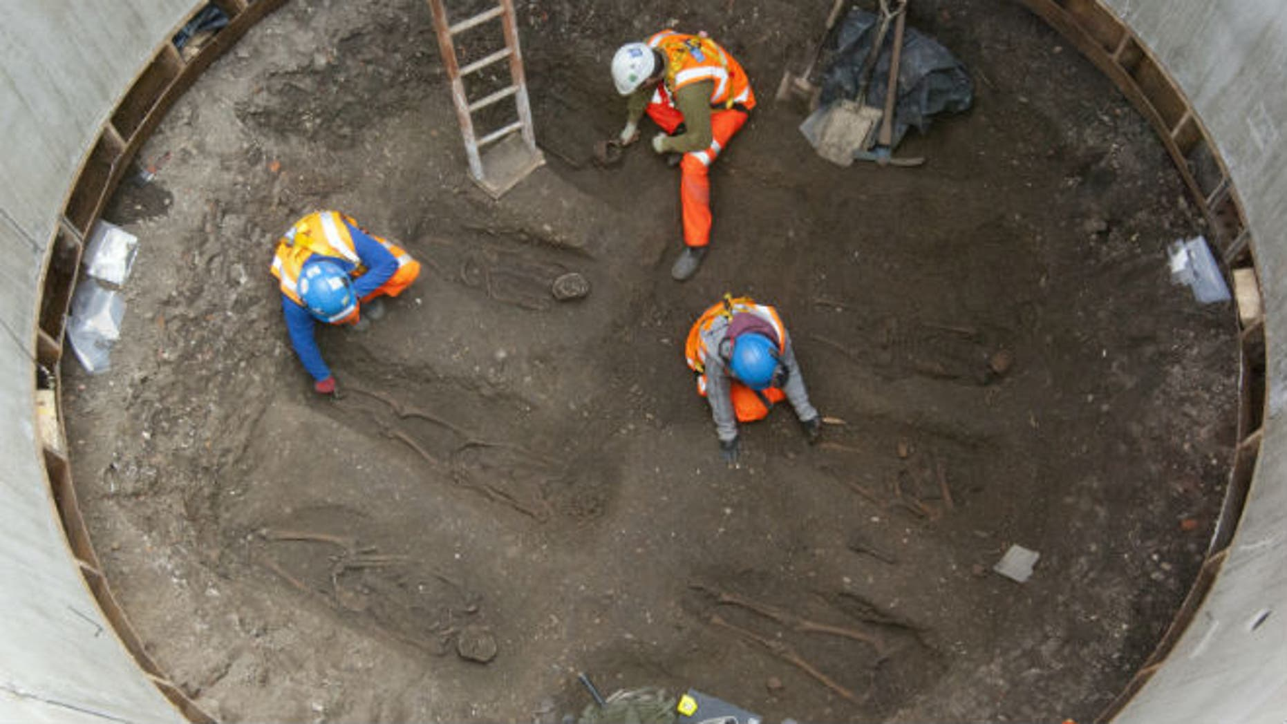 """Archaeologists work on unearthed skeletons in the Farringdon area of London in this undated handout photograph released March 15, 2013. Archaeologists said on Friday they had found a graveyard during excavations for a rail project in London which might hold the remains of some 50,000 people killed by the """"Black Death"""" plague more than 650 years ago. REUTERS/Crossrail/Handout"""