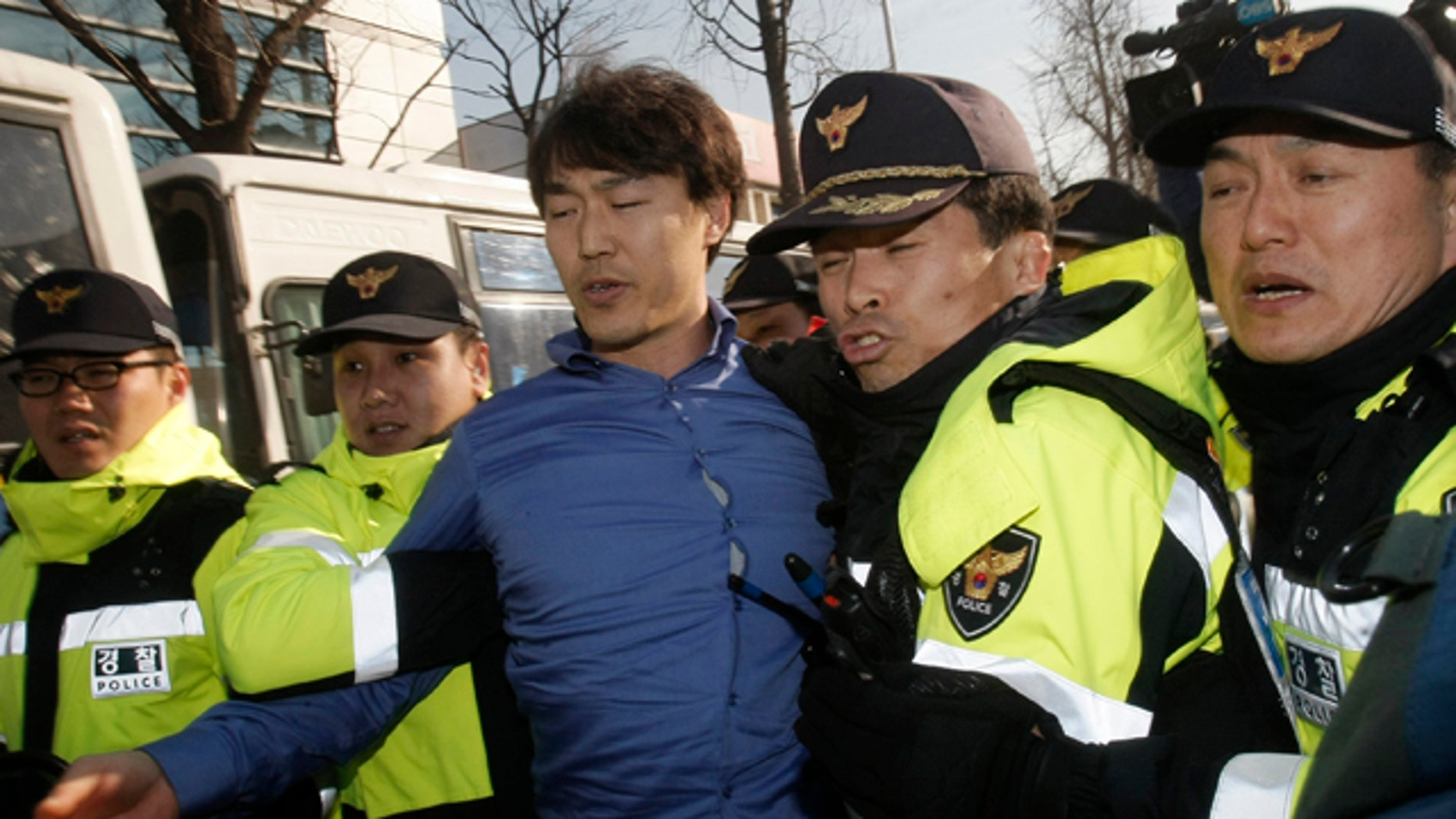 Dec. 13: A South Korean protester, center, is detained by police officers after ramming his car into a police bus guarding Chinese Embassy during a rally to denounce a Chinese fisherman, who killed a South Korea Coast Guard officer when a boat was stopped for suspected illegal fishing in South Korean waters, in Seoul.