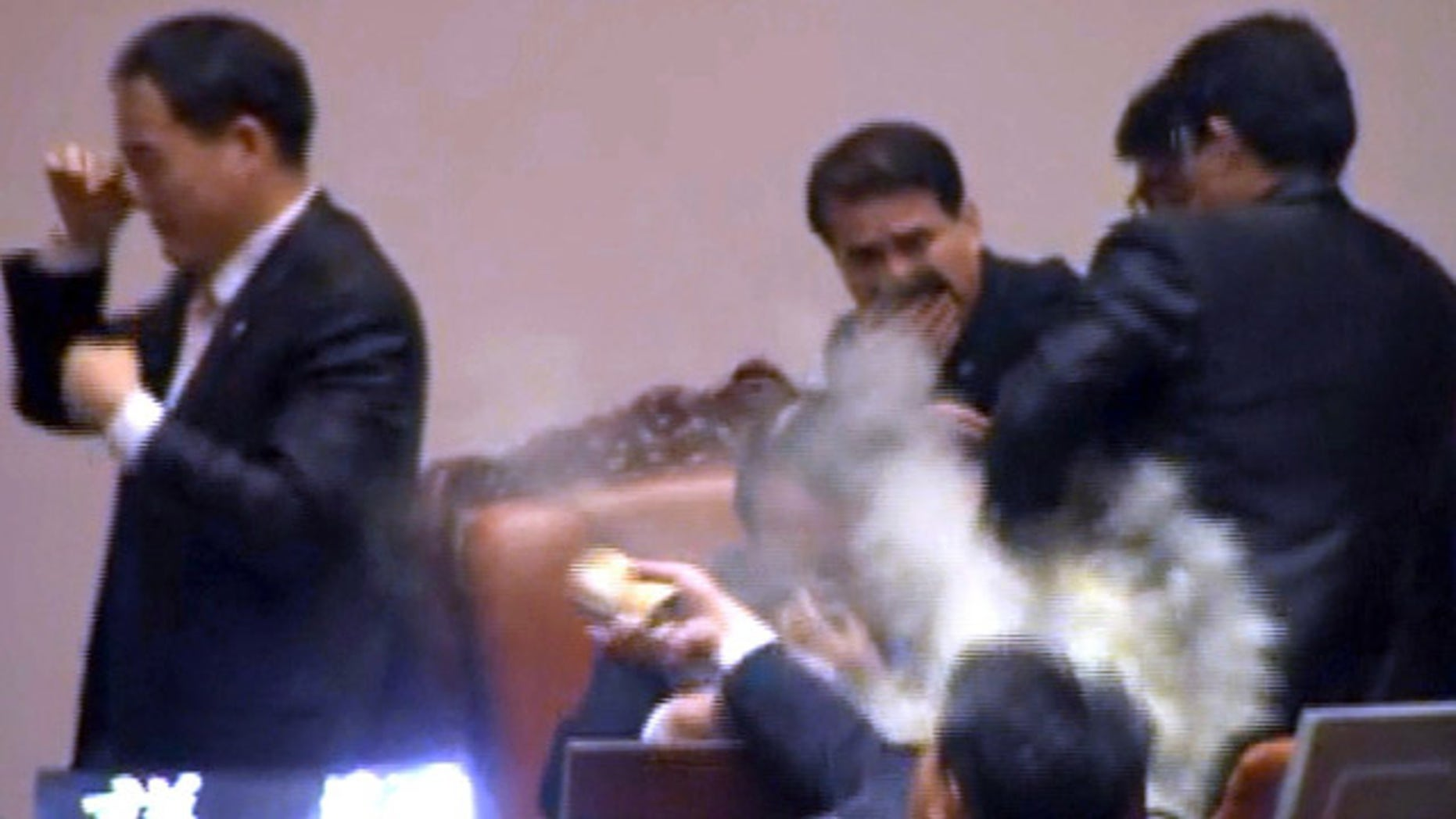 Nov. 22, 2011: Rep. Kim Seon-dong, bottom, of the opposition Democratic Labor Party, explodes tear gas in front of the speaker's chair to block National Assembly Vice Speaker Chung Eui-hwa, center, from pushing for the procedure to handle a pending bill on ratification of a South Korea-U.S. free trade agreement at the National Assembly in Seoul, South Korea.