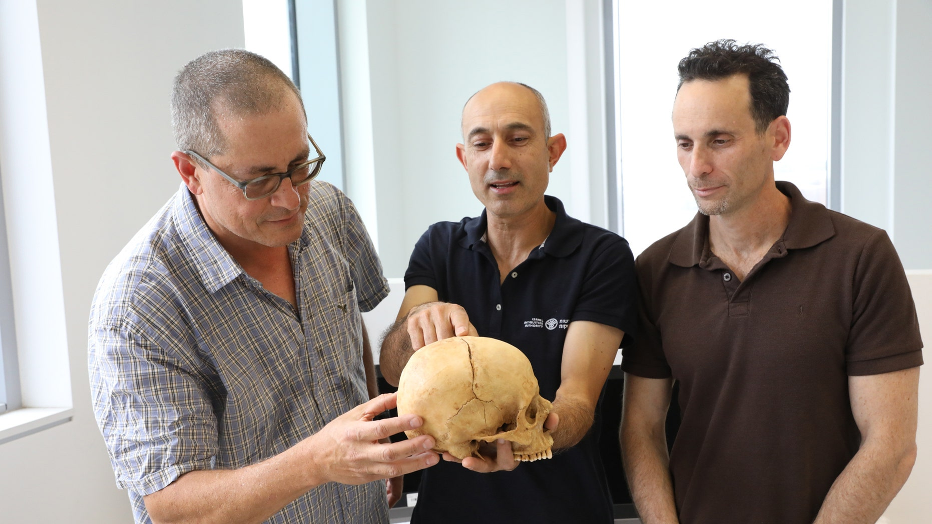 Left to right: Prof. Boaz Zissu of Bar-Ilan University, Dr. Yossi Nagar of the Israel Antiquities Authority and Dr. Haim Cohen of the National Center for Forensic Medicine and Tel Aviv University with the skull (Israel Antiquities Authority)