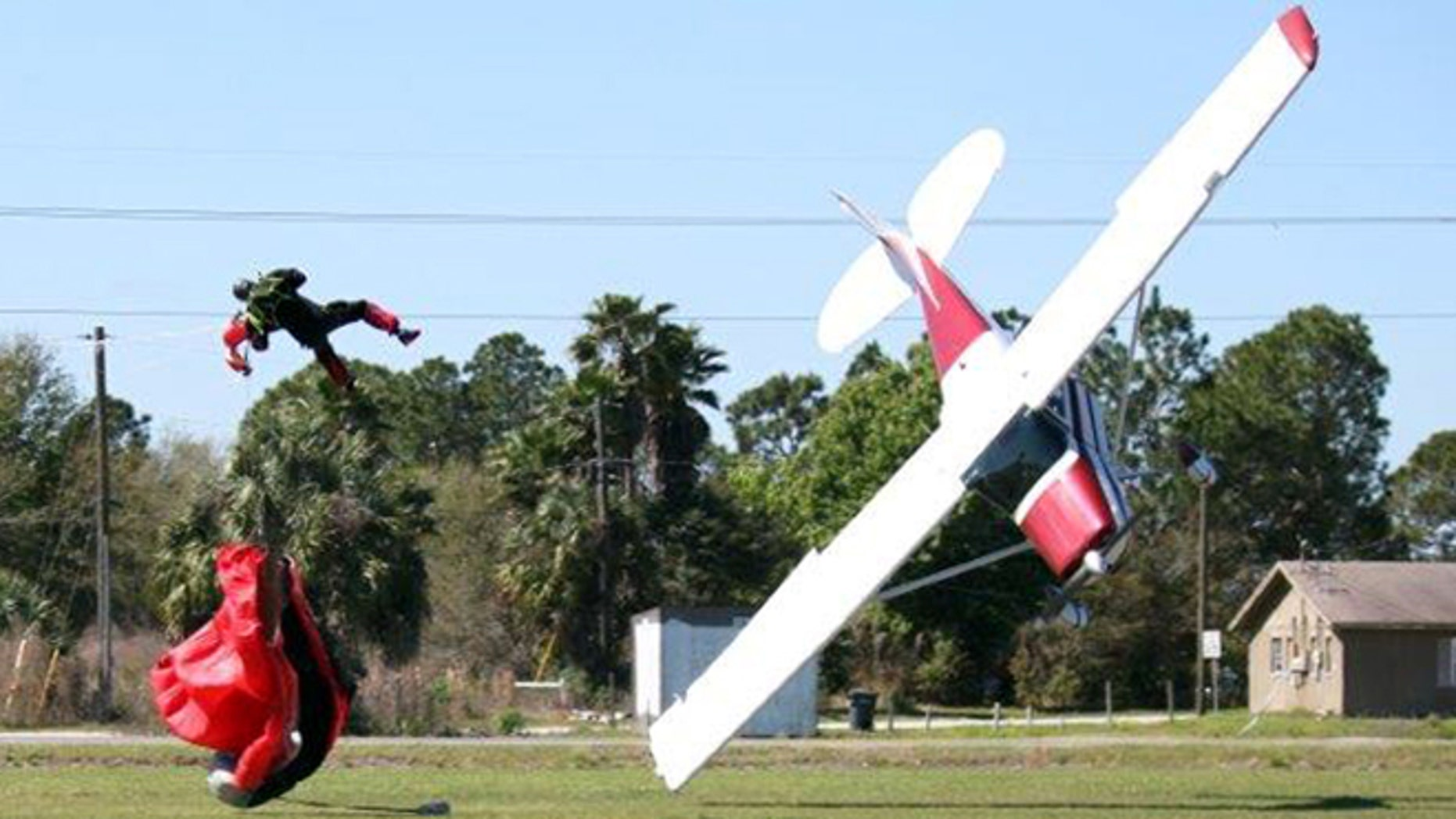 March 8, 2014: This photo released by the Polk County Sheriff's Office shows a plane nose-diving into the ground after getting tangled with a parachutist, left, at the South Lakeland Airport in Mulberry, Fla. Both the pilot and jumper hospitalized with minor injuries.
