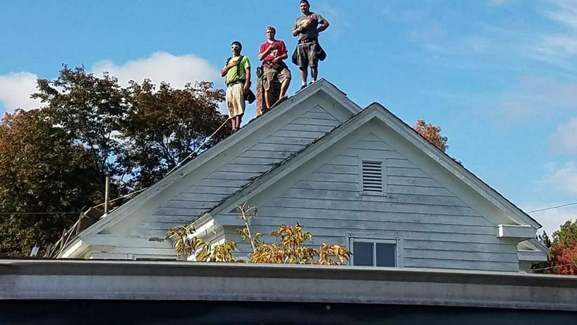 Three Maine roofers stand for the playing of the national anthem.