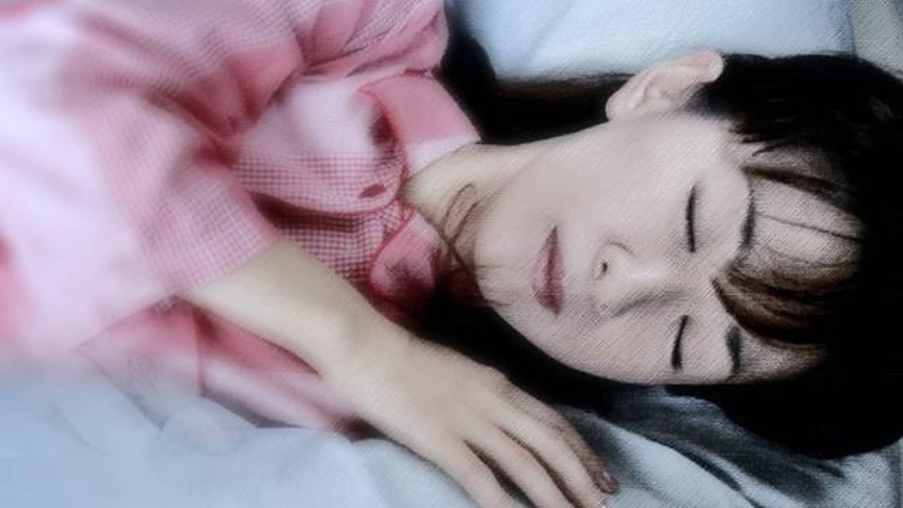 """Junko Suzuki, a radio DJ, demonstrates how she sleeps with a """"Boyfriend's Arm Pillow"""" in Tokyo Friday, Sept. 24, 2004.  The pillow manufactured by linen maker Kameo Corp. consists of a headless torso and a stuffed arm that curls around the sleeper. It might make some people uneasy but have sold about 1,000  in Japan since the product went on the market last December. The maker says the pillow is not only an emotional comfort, but that its shape keeps the body balanced by supporting the sleeper from both sides. (AP Photo/Koji Sasahara)"""