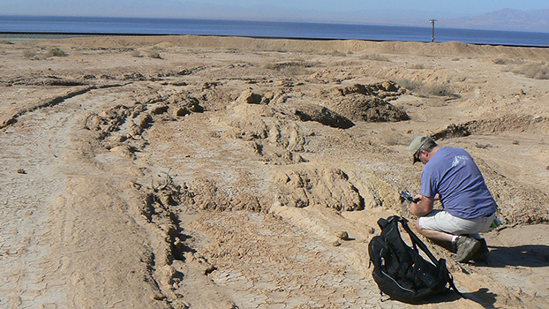 Geologist Neal Driscoll taking measurements of the onshore sediment layers along the eastern edge of the Salton Sea.