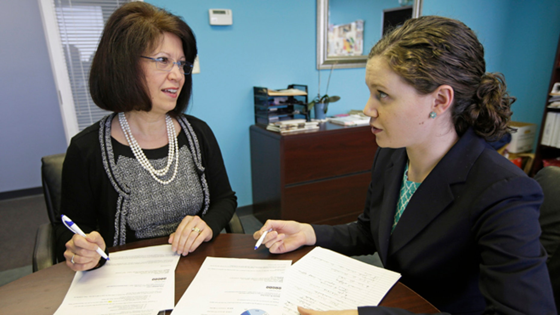 In this Jan. 22, 2014 photo, Tillie Hidalgo Lima, chief executive officer of Best Upon Request, a concierge services provider, left, works with marketing director Jessica Lima Bollin in their offices in Cincinnati. A mentoring program created by the Cincinnati USA Regional Chamber called a minority business accelerator has helped Lima get contracts with Fifth Third Bank Corp. and the Cincinnati Children's Hospital Medical Center. (AP Photo/Al Behrman)