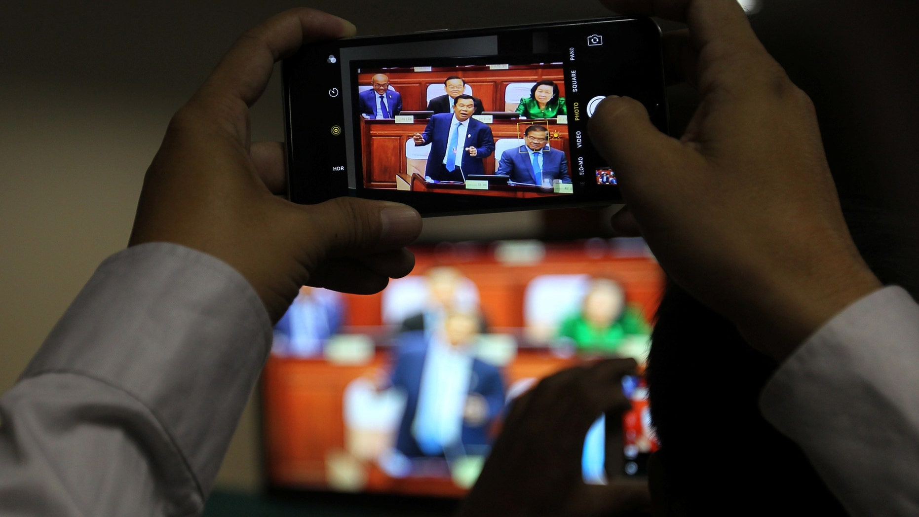 File photo: A man uses a smartphone to take a picture of Cambodia's Prime Minister Hun Sen from a television screen during a plenary session at the National Assembly of Cambodia, in central Phnom Penh, January 31, 2017. (REUTERS/Samrang Pring)