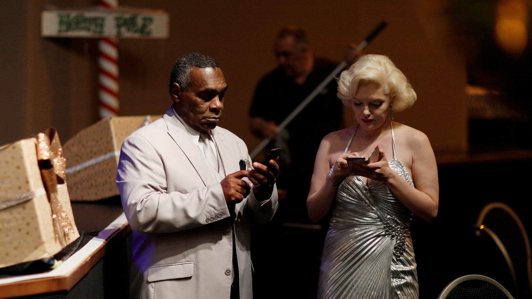 "File photo: Performers dressed as Marilyn Monroe and Louis Armstrong check their smartphones before a ""Stars in Concert"" show at the Estrel hotel in Berlin, Germany, December 7, 2016. (REUTERS/Hannibal Hanschke)"