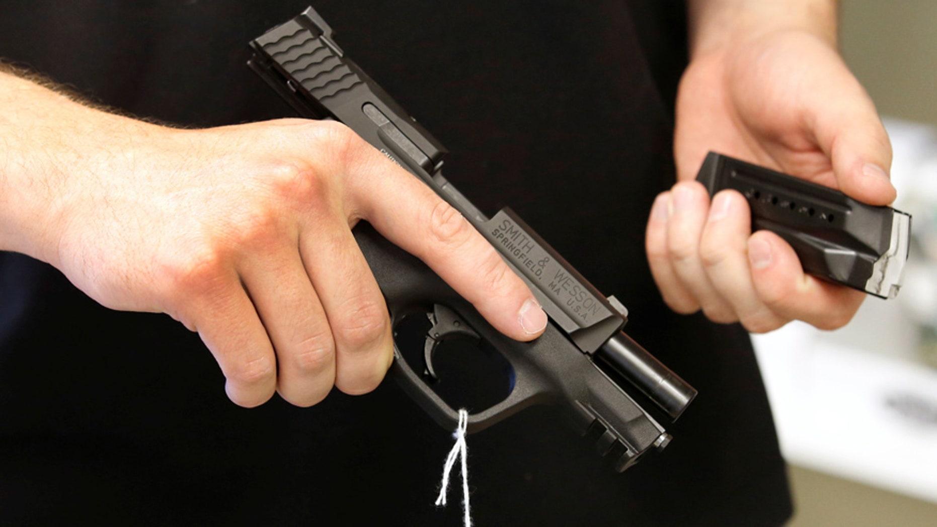 "June 21, 2016: Salesman Ryan Martinez hold an Smith & Wesson handgun and magazine at the ""Ready Gunner"" gun store in Provo, Utah."
