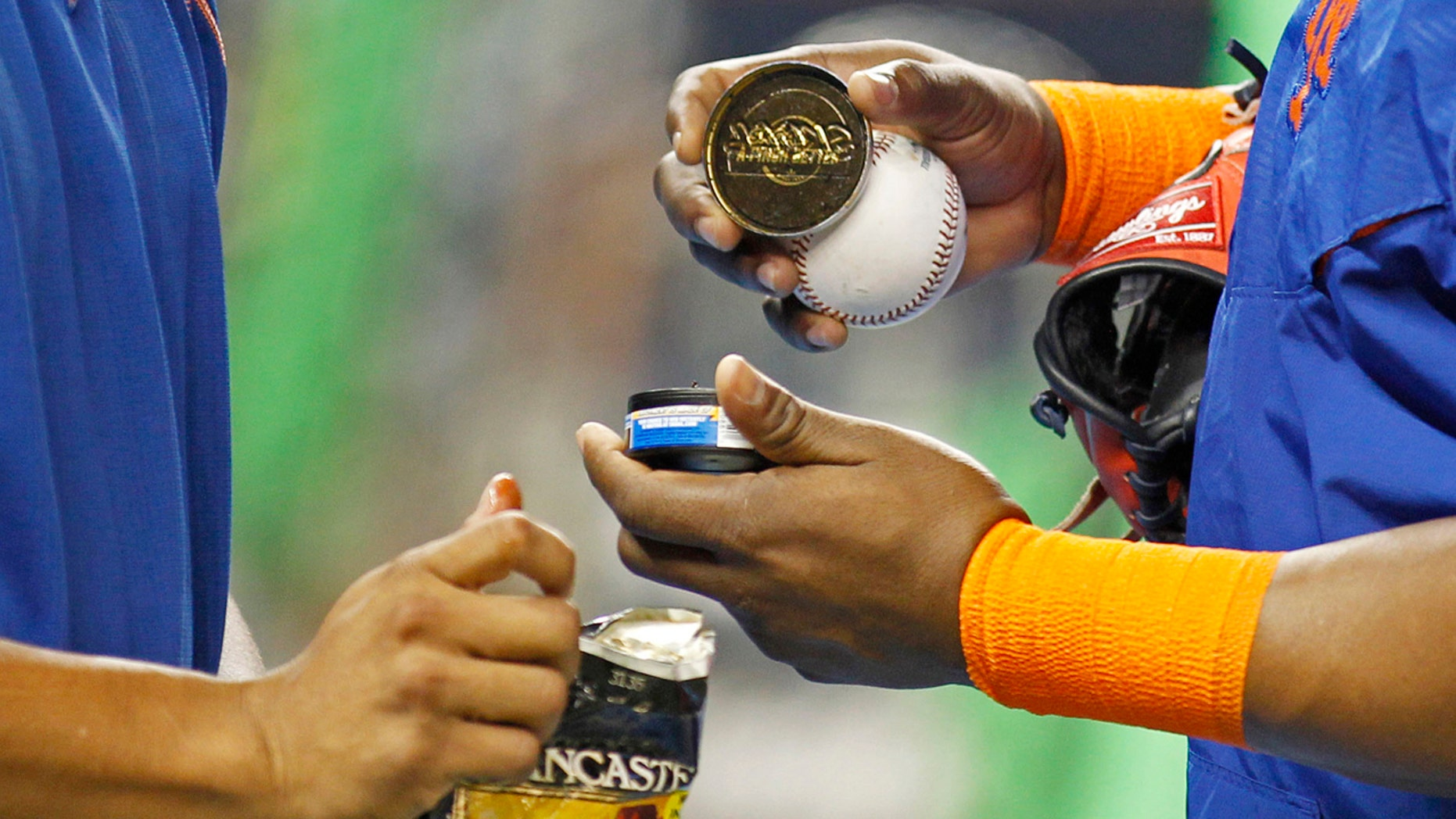 FILE - In this Sept. 5, 2015, file photo, New York Mets players hold tobacco products during batting practice before the team's baseball game against the Miami Marlins in Miami.