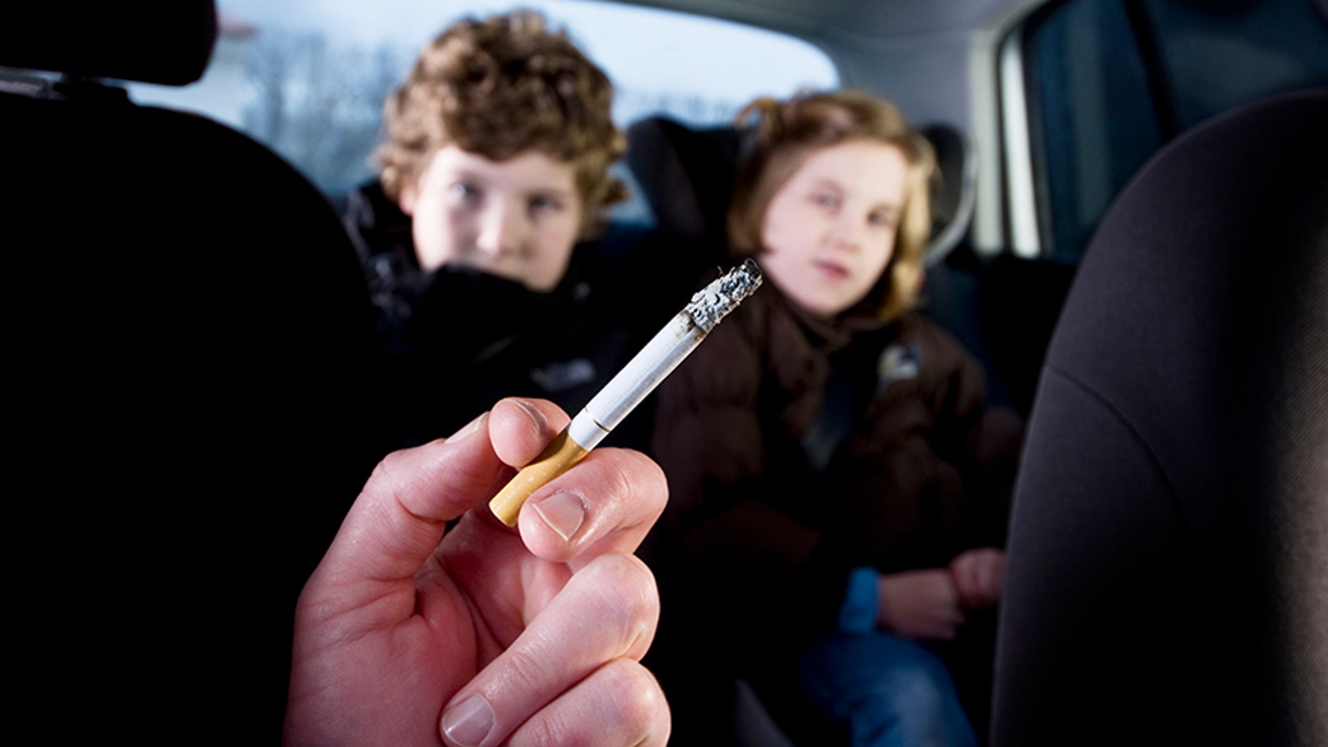 Two young children being subjected to the effects of passive smoking from their mother's cigarette.