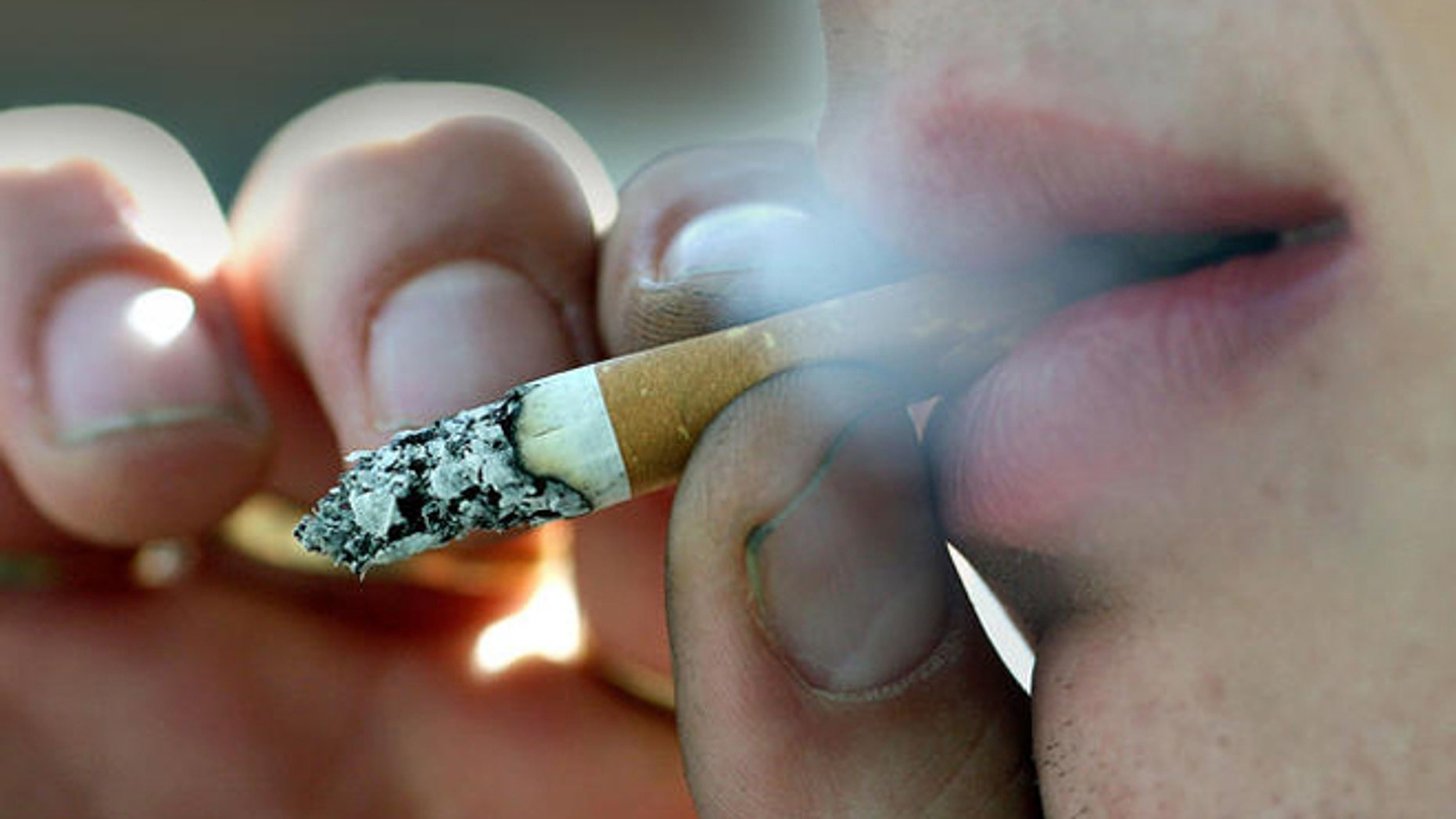 A person smokes outside his place of work in Belfast, Northern Ireland, Monday, April, 30, 2007.  A smoking ban  in all public places has come into effect from Monday in Northern Ireland.  (AP Photo/Peter Morrison)
