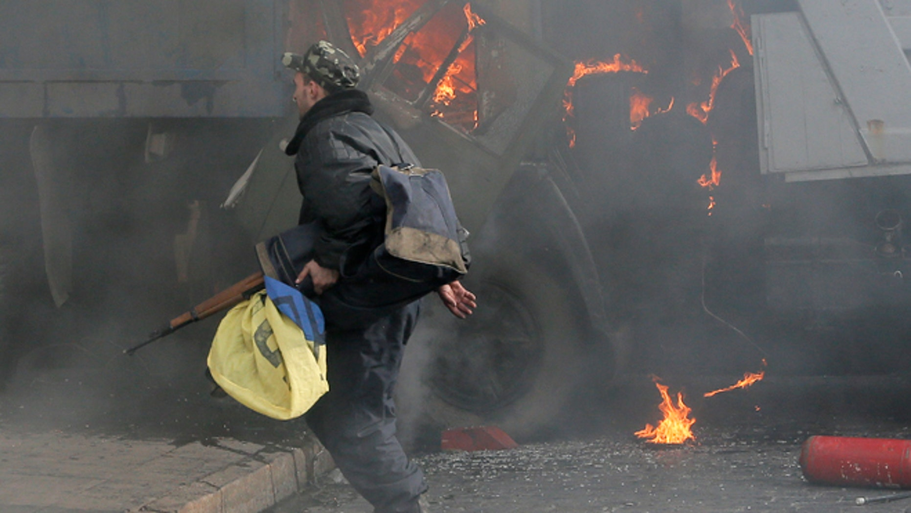 Feb. 21, 2014 In this file photo, a man with a gun runs along a street during a clash between opposition protesters and riot police at a burning barricades near the Presidential office in Kiev, Ukraine.