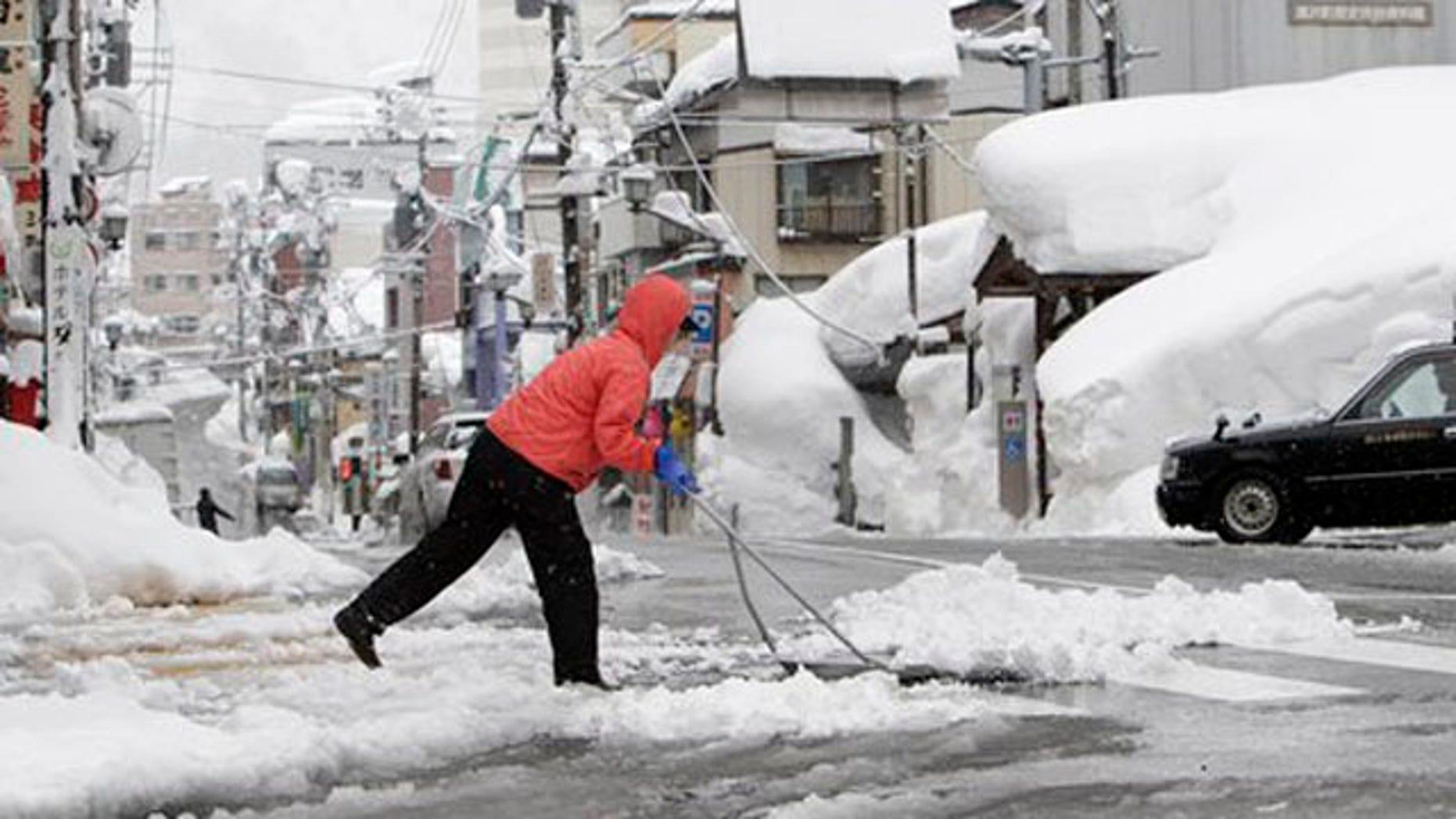 Feb. 1, 2012: A woman removes snow off a street in Yuzawa, Niigata prefecture, north of Tokyo.