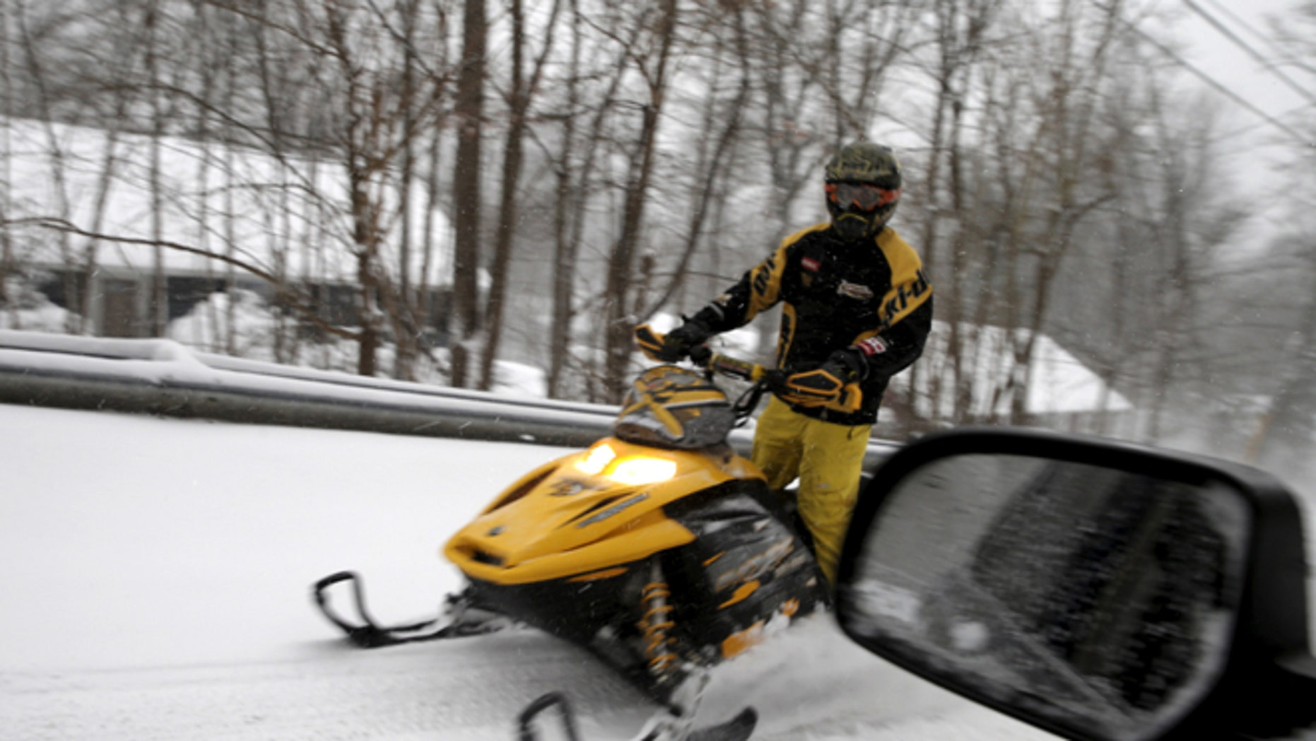 A man rides a snowmobile on a street in the village of Upper Nyack, New York, a northern suburb of New York City along the Hudson river January 23, 2016.