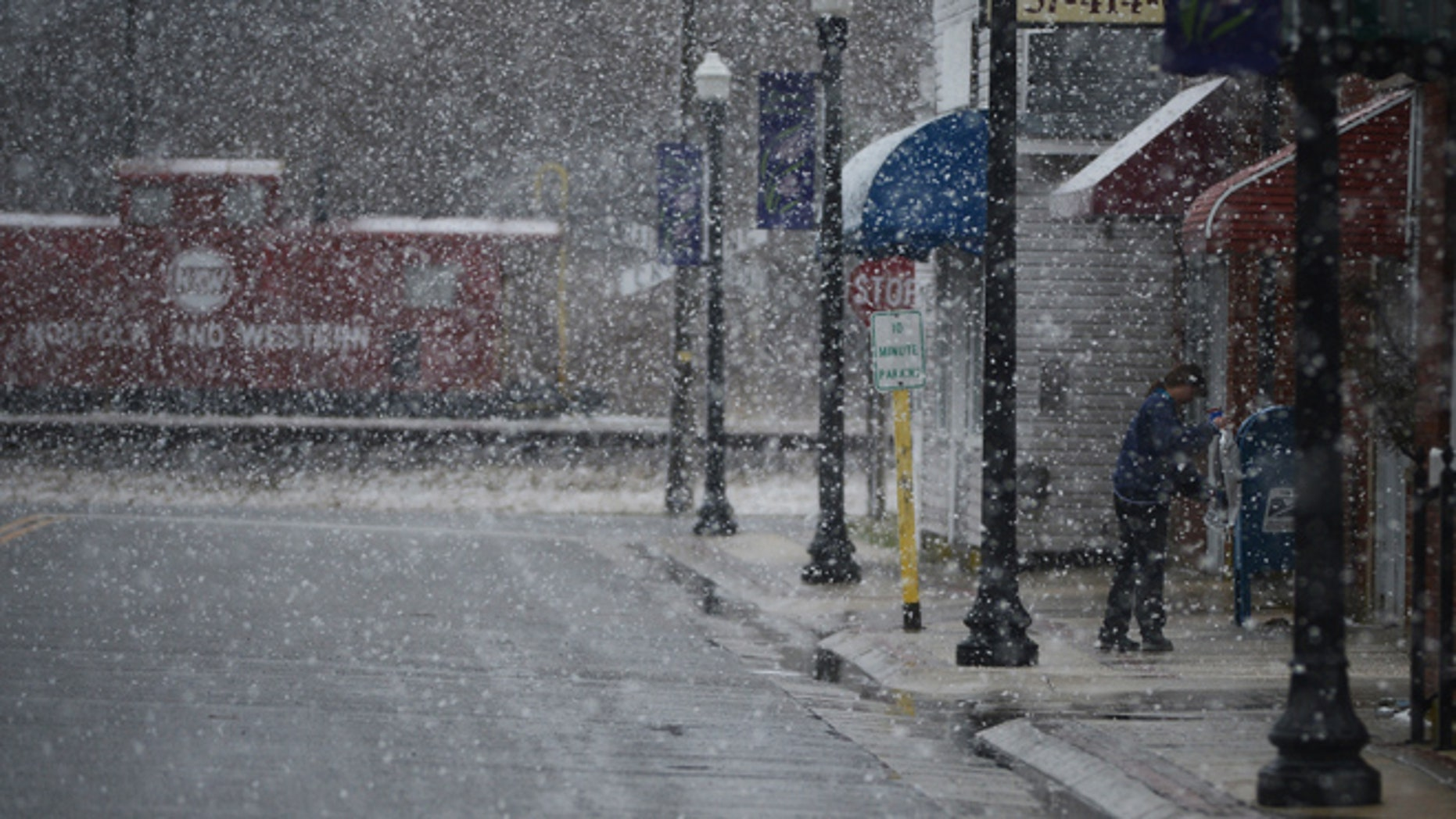 March 25, 2014: U.S. Postal employee Janeen Long salts and sands the sidewalk in front of the Exmore, Va. Post Office during a heavy snow fall.