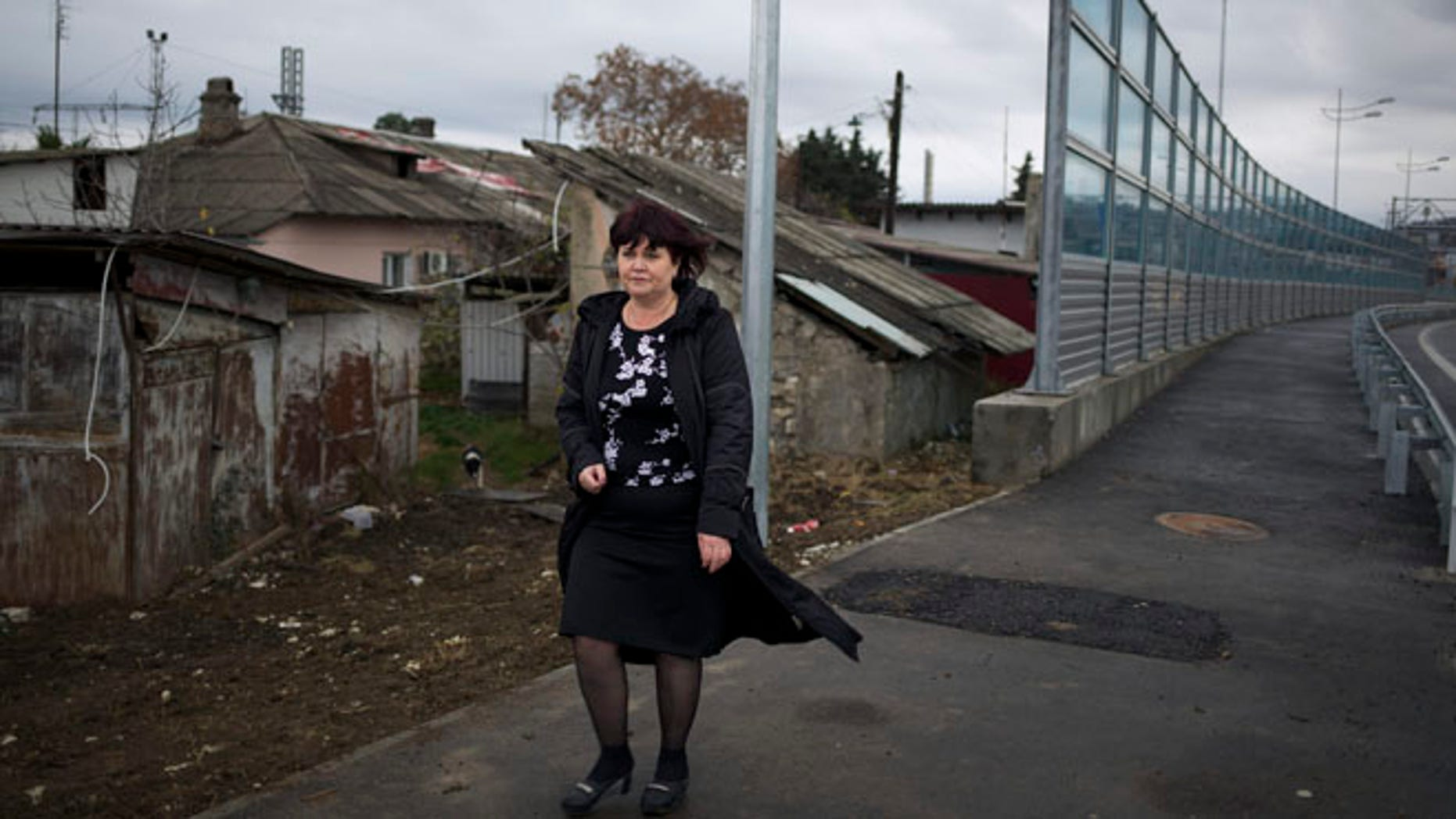 Nov. 27, 2013:  Irina Kharchenko walks away from her house beside the screen separating the yard of her house and a federal highway in the village Vesyoloye outside Sochi, Russia. As the Winter Games are getting closer, many Sochi residents are complaining that their living conditions only got worse and that authorities are deaf to their grievances.