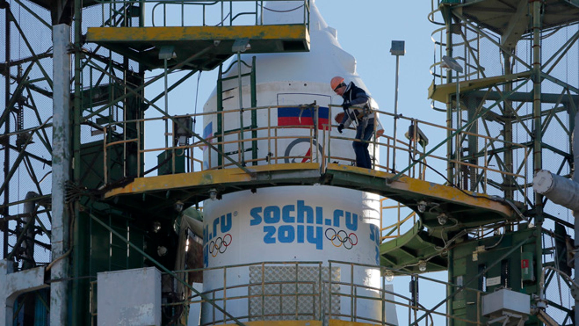 Nov. 5, 2013: A Baikonur Cosmodrome staff member works at Russia's Soyuz-FG booster rocket, emblazoned with the emblem of the Winter Olympics in Sochi, loaded with Soyuz TMA-11M space capsule that will carry new crew to the International Space Station (ISS) as the rocket is transported from hangar to the launch pad at the Russian leased Baikonur cosmodrome, Kazakhstan. For the first time, it will also carry an Olympic torch to space as part of the ongoing Olympic torch relay. The torch will be brought back along with the station's current crew. The rocket is scheduled to blast off on Thursday, Nov. 7.