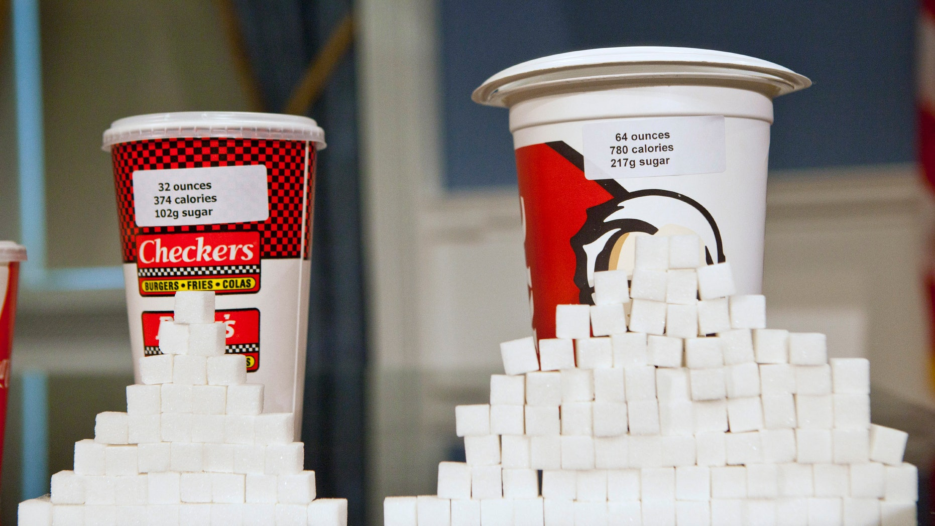Soft drink cups sized (L-R) at 32 ounces and 64 ounces are displayed at a news conference at City Hall in New York, May 31, 2012. (REUTERS/Andrew Burton)