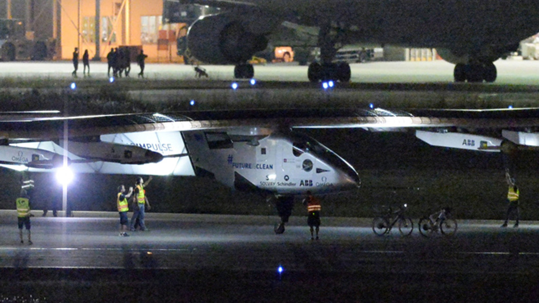 June 1, 2015: The Solar Impulse 2 project staff members gather around the aircraft as it lands the Nagoya Airport in Toyoyama, near Nagoya, central Japan.
