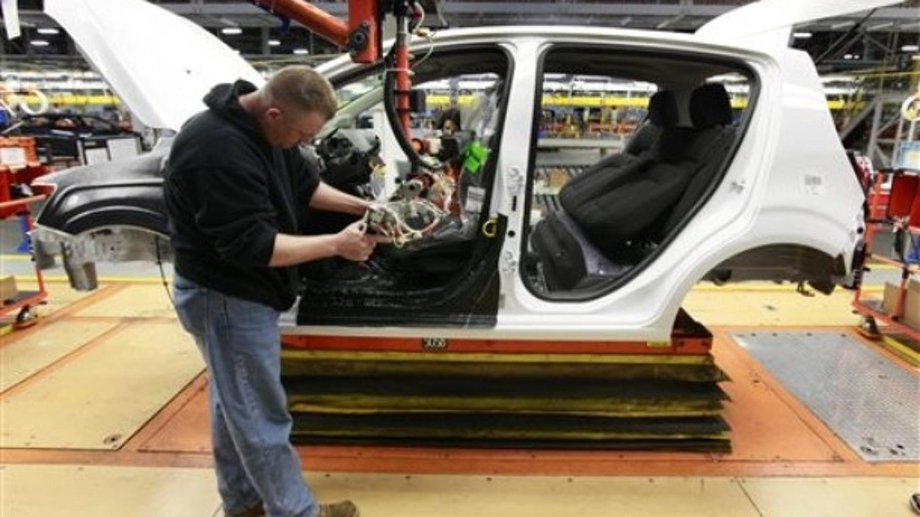 In this May 19, 2011 photo, line worker David Beebe works on a pre-production Chevrolet Sonic at the General Motors Orion Assembly plant in Orion Township, Mich. General Motors said Friday, June17, 2011, that pricing for its new Chevrolet Sonic will start at just under $15,000. The sub-compact car is set to hit dealer lots this fall. (AP Photo/Paul Sancya)