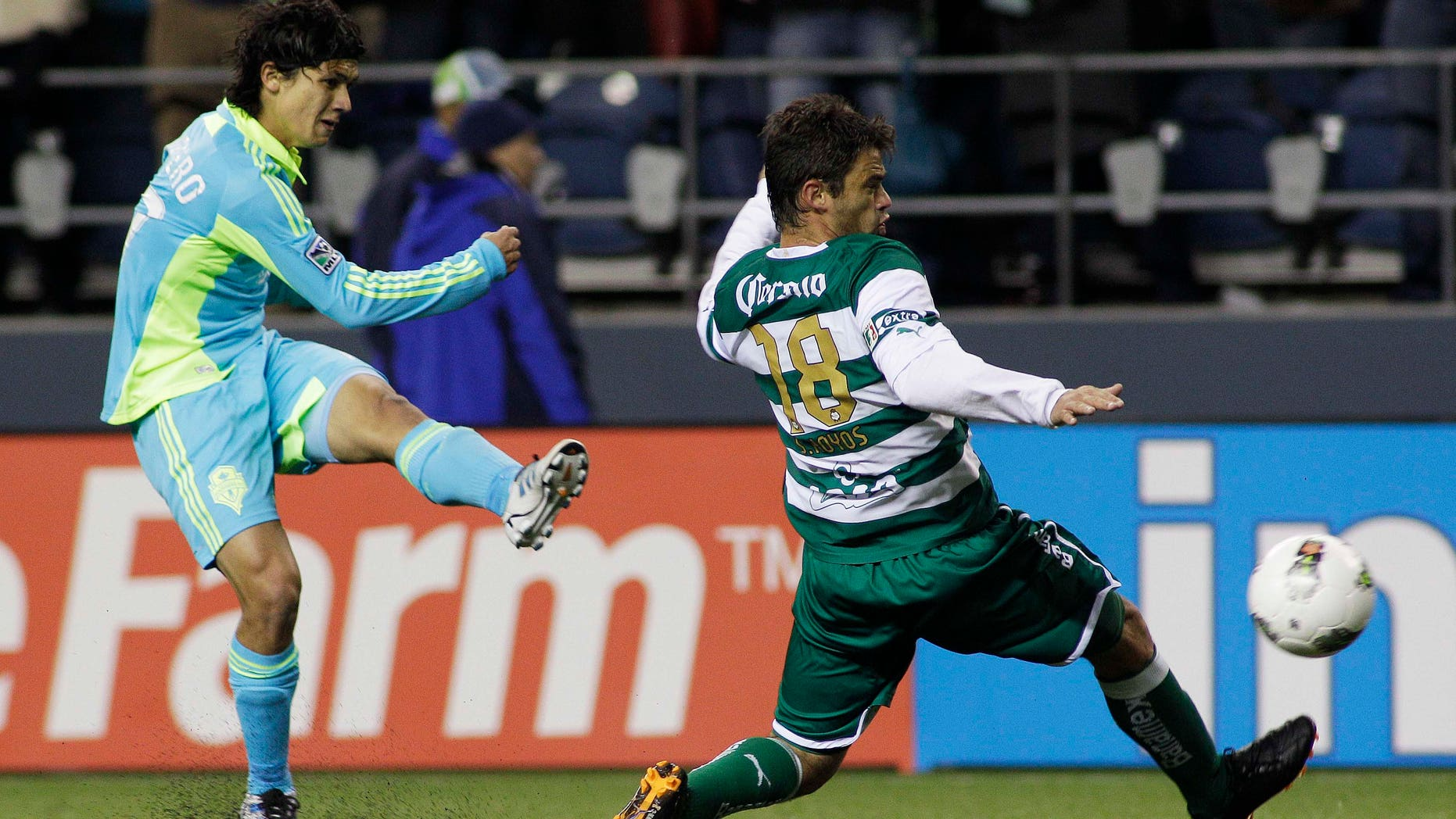 Seattle Sounders FC's Fredy Montero, left, shoots past Santos Laguna's Santiago Hoyos in the second half of a CONCACAF Champions League quarterfinal soccer match, Wednesday, March 7, 2012, in Seattle. The Sounders beat Santos, 2-1.