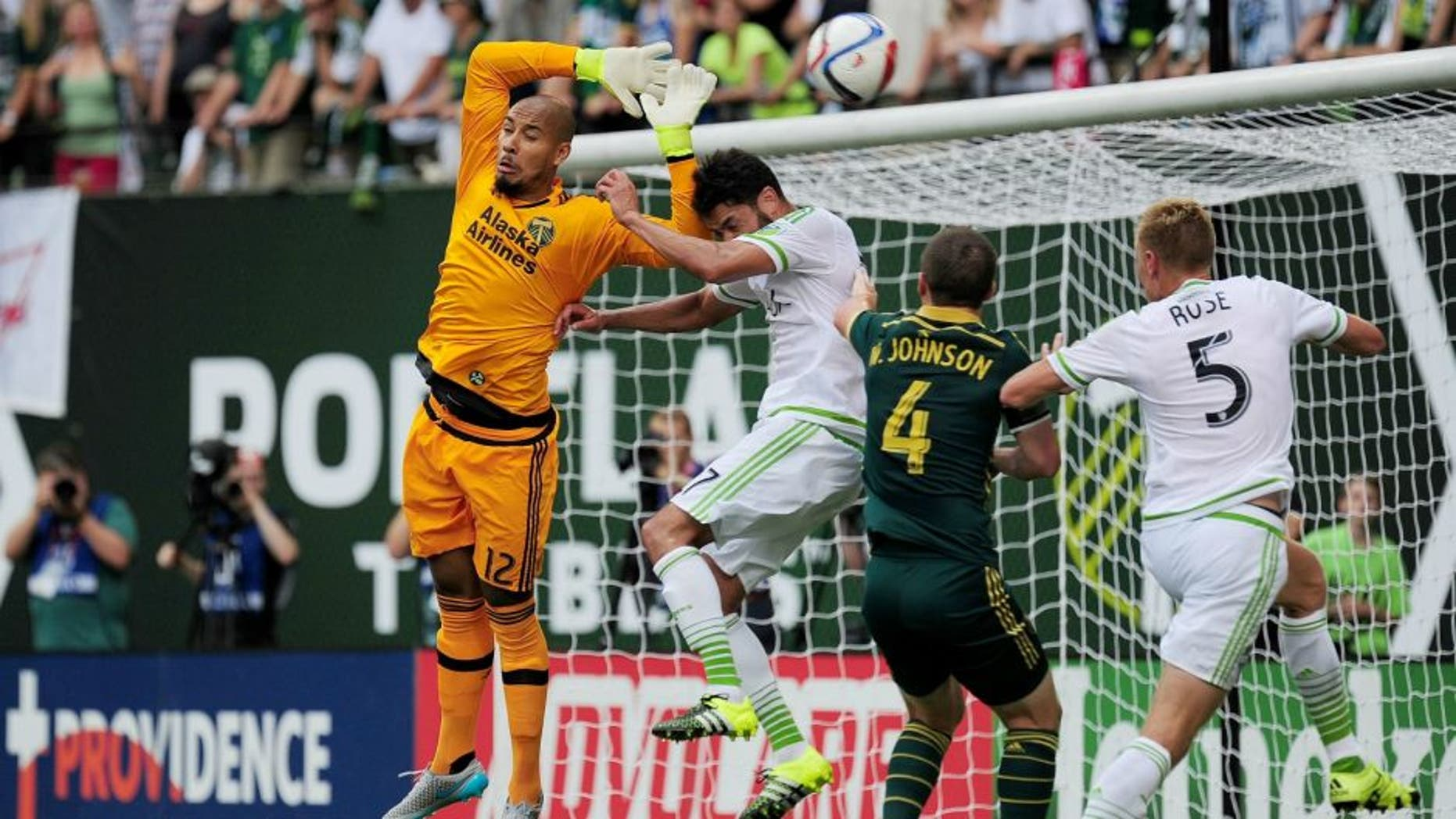 Jun 28, 2015; Portland, OR, USA; Portland Timbers goalkeeper Adam Kwarasey (12) makes sure the ball is out of reach during the first half of the game against the Seattle Sounders at Providence Park. Mandatory Credit: Godofredo Vasquez-USA TODAY Sports