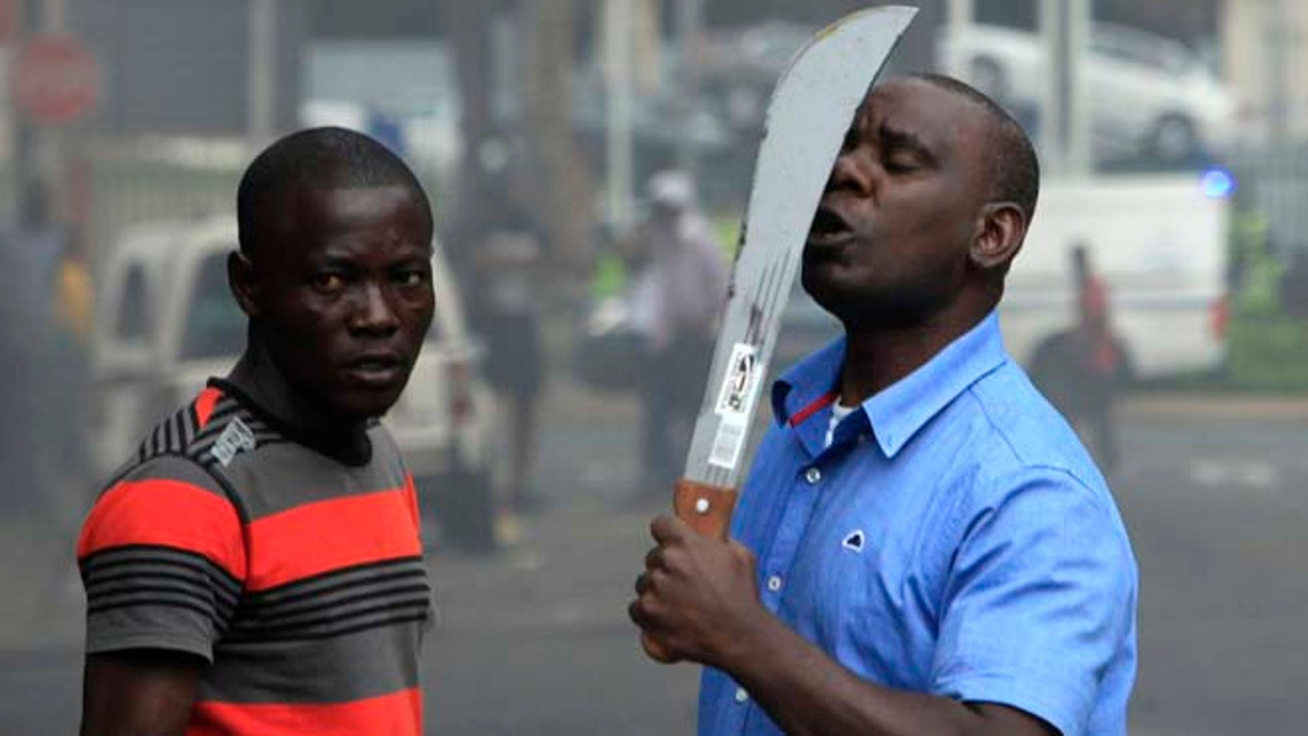April 14, 2015: In this photo taken in  Durban, South Africa, an immigrant armed with a machete on a street during clashes with police and in search of locals that attacked foreign shop owners in the city center.