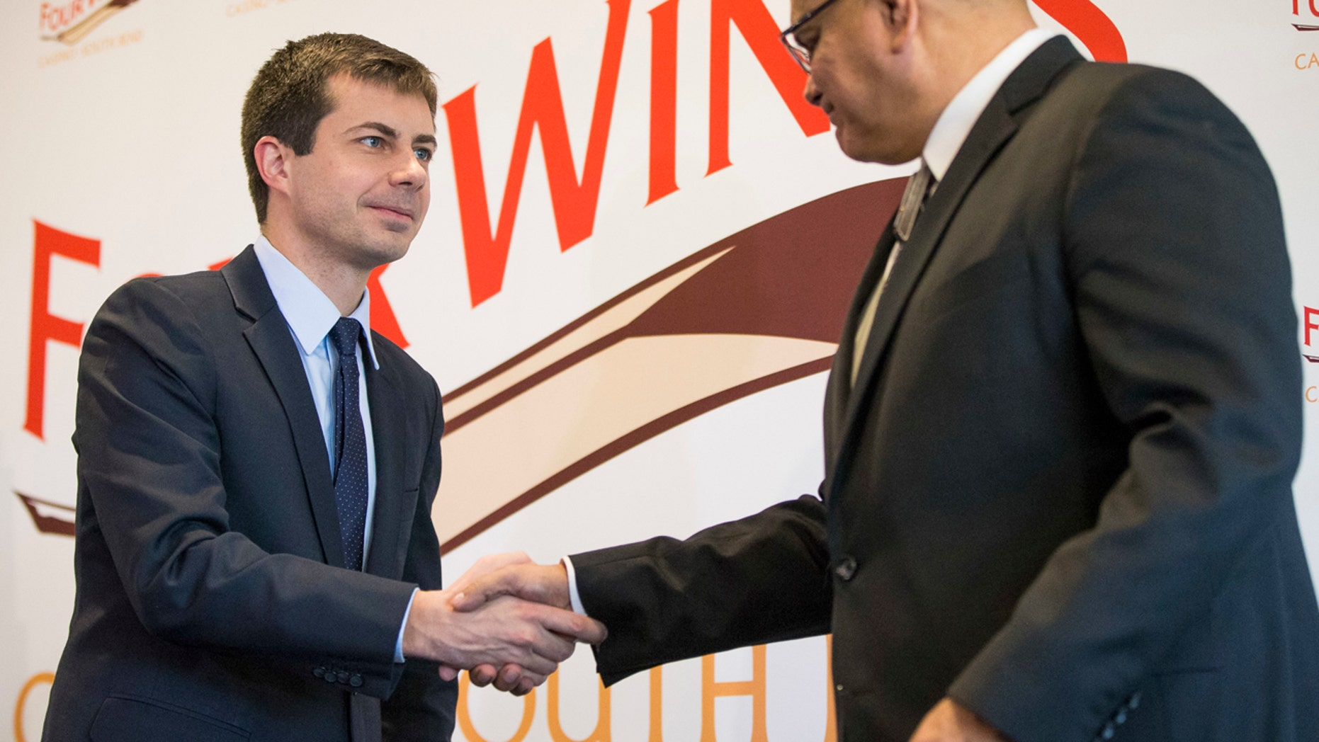 South Bend Mayor Pete Buttigieg, left, shakes hands with John Warren, chairman of the Pokagon Band, during news conference, Wednesday, Dec. 7, 2016, in South Bend, Ind.