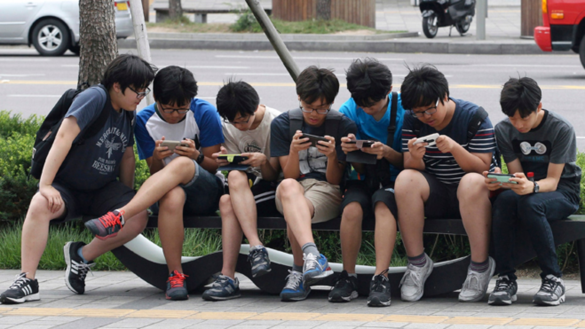 July 16, 2015: South Korean high school students play games on their smartphones on a bench on the sidewalk in Seoul, South Korea. The most widely used child surveillance app in South Korea is being quietly pulled from the market after security specialists raised serious concerns about the program's safety.
