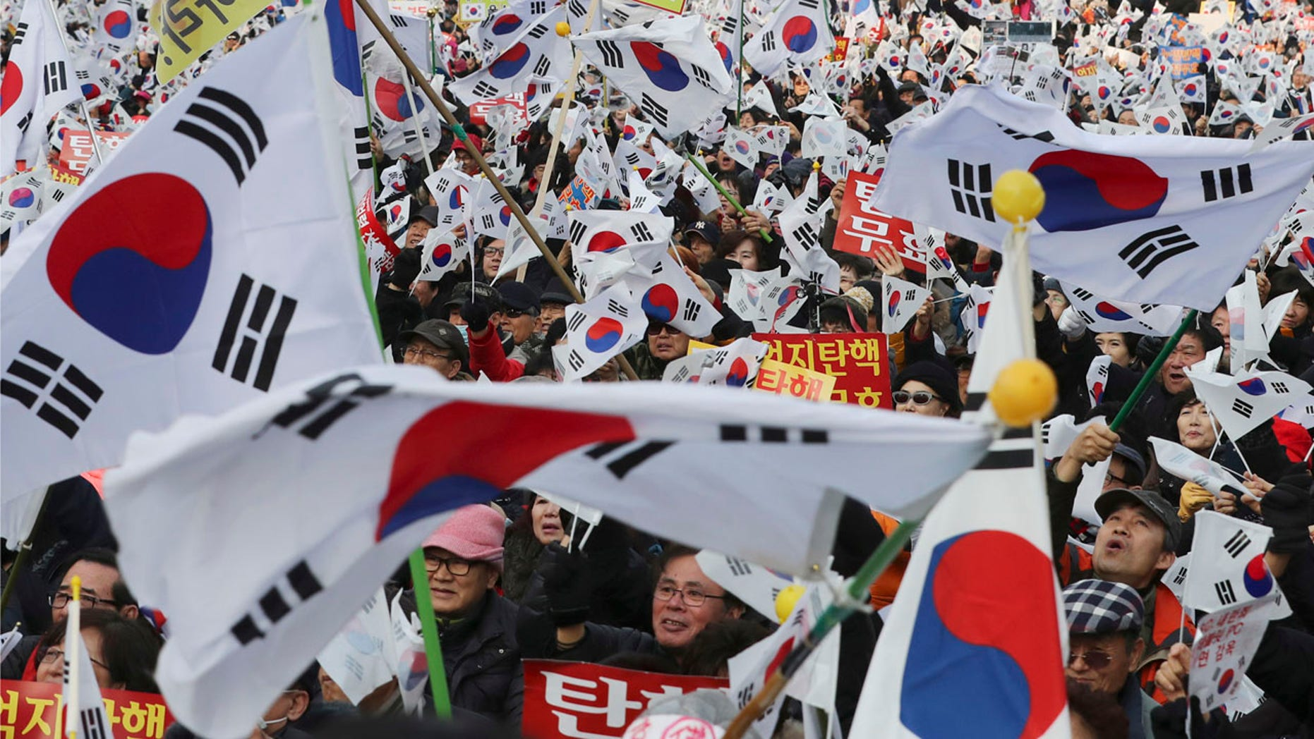 Supporters of South Korean President Park Geun-hye wave their national flags during a rally opposing her impeachment in Seoul, South Korea, Saturday, Dec. 31, 2016.
