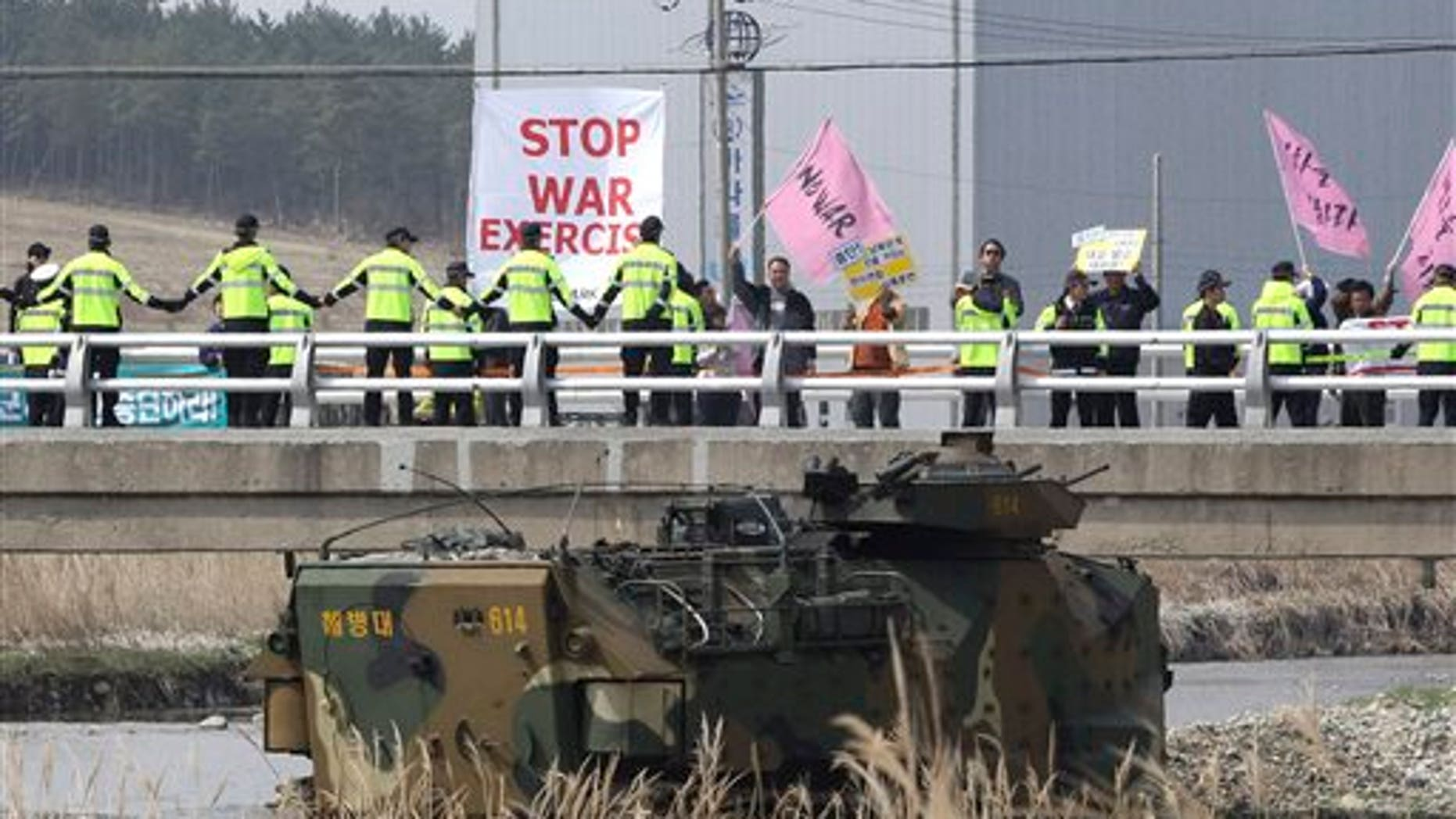 Anti-war protesters stage a rally during the U.S.-South Korea joint landing exercises called Ssangyong as part of the Foal Eagle military exercises in Pohang, South Korea, Monday, March 31, 2014. South Korea on Monday returned fire into North Korean waters after shells from a North Korean live-fire drill fell south of the rivals' disputed western sea boundary, a South Korean military official said. (AP Photo/Ahn Young-joon)