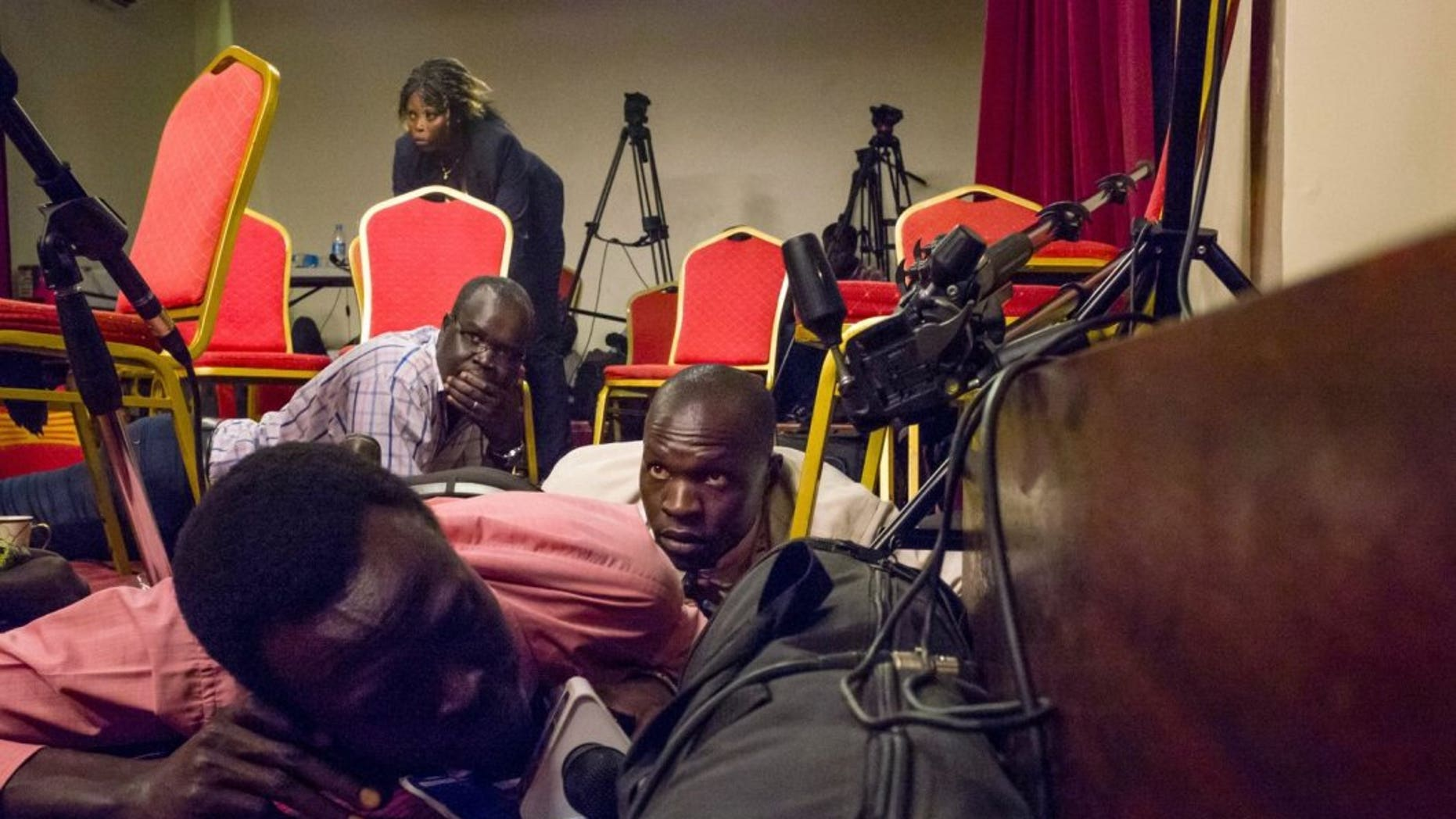 Journalists lie on the floor of a press room in the South Sudan presidential palace after shots were heard on Friday.