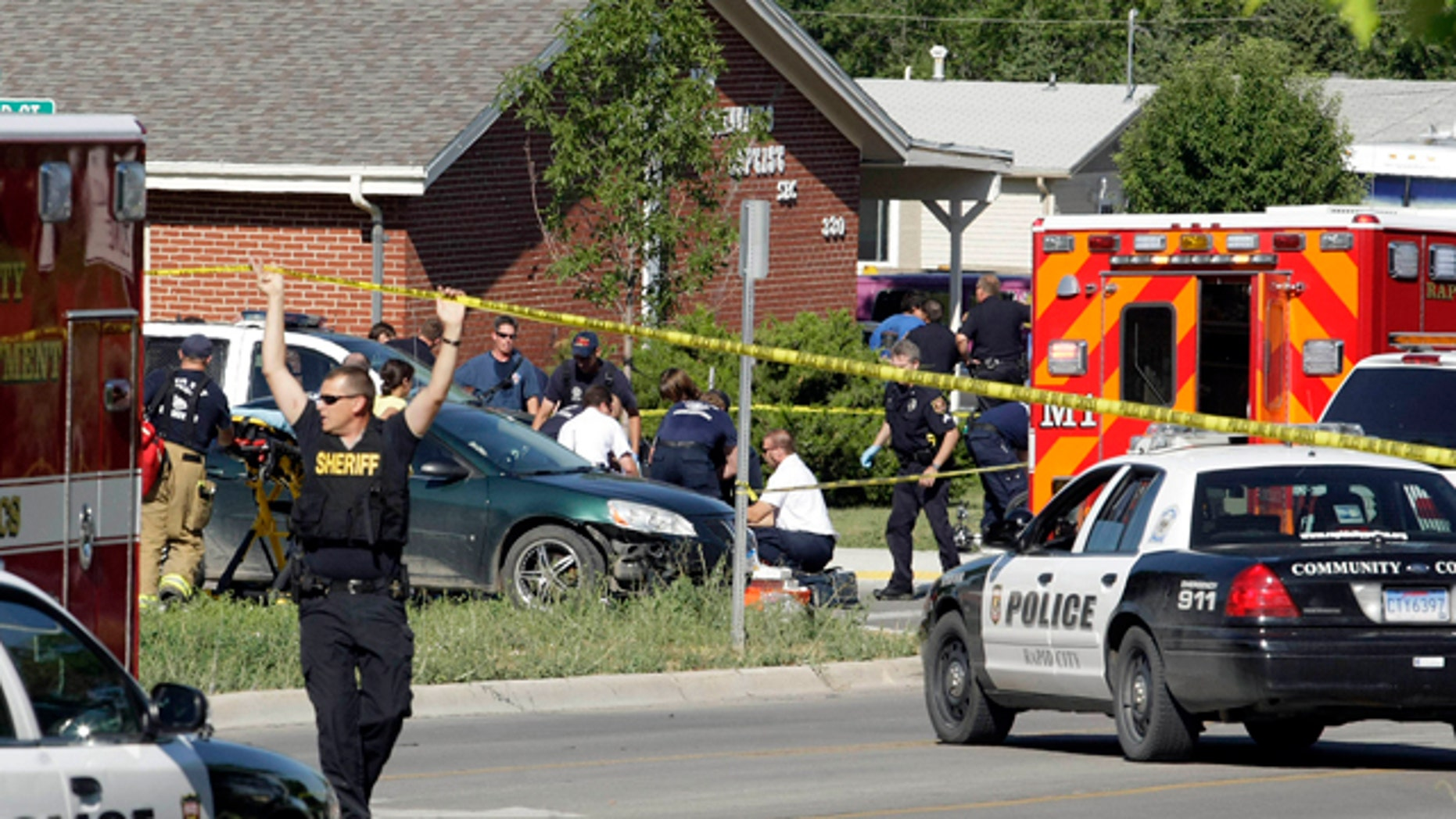 Aug. 2: Rapid City Firefighter/Paramedics and Rapid City Police Department personnel respond to shootings at the intersection of Anamosa and Greenbriar streets, in Rapid City, S.D. A Rapid City police officer was killed and two others were seriously wounded after a shootout with a man during a routine stop in the South Dakota city, authorities said late Tuesday. Gunfire erupted about 10 minutes after the three officers approached four people at an intersection.