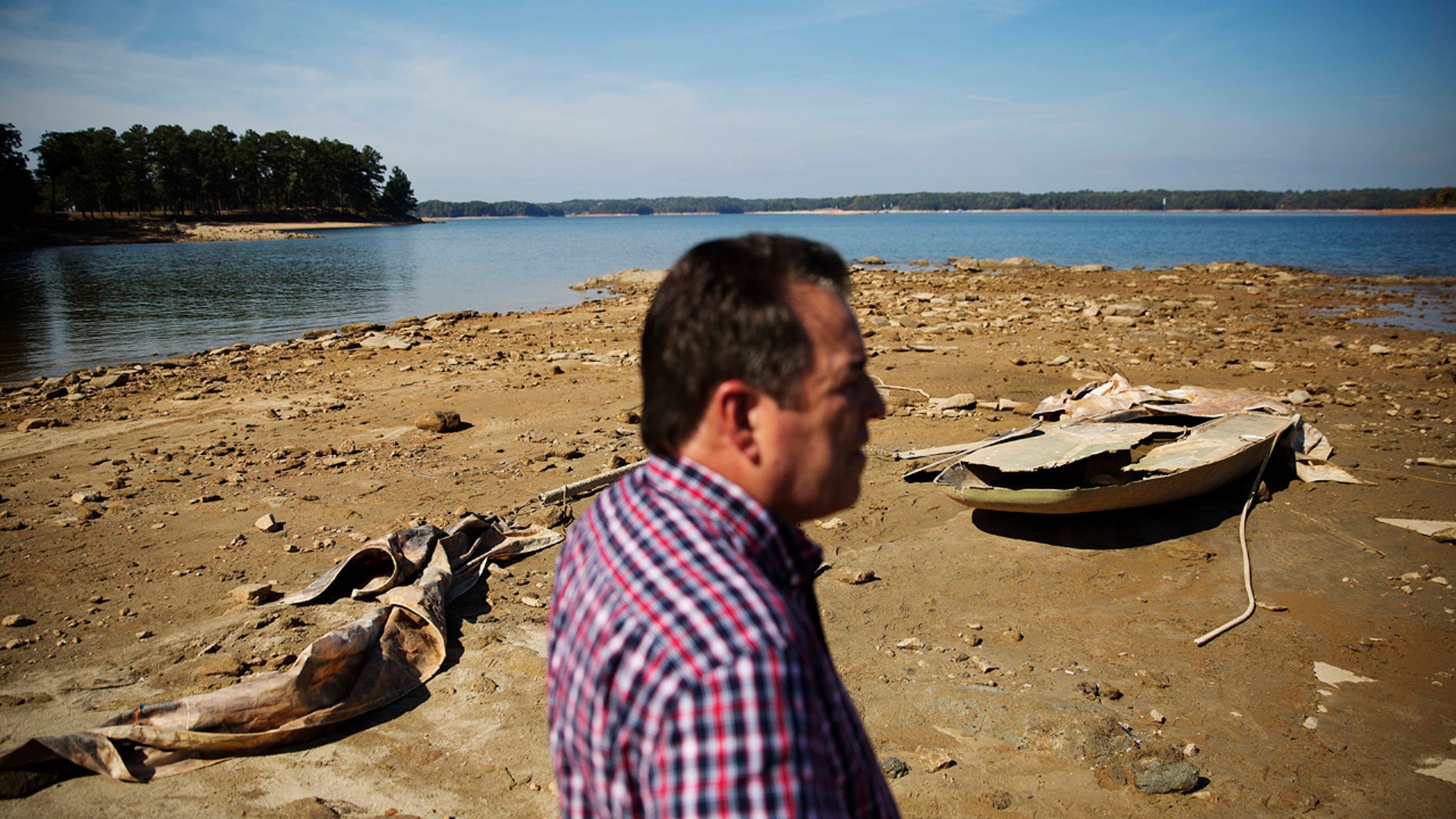 In this Wednesday, Oct. 26, 2016, file photo, a sunken boat is exposed by receding water levels on Lake Lanier as U.S. Army Corps of Engineers Natural Resources Manager Nick Baggett looks on in Flowery Branch, Ga.