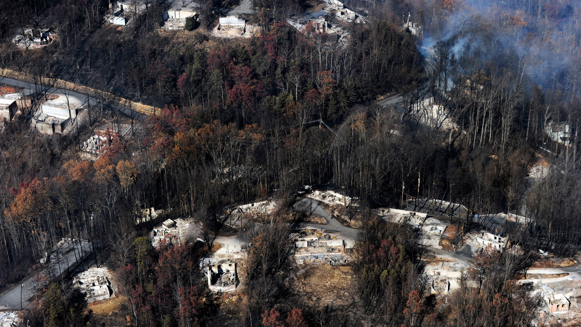 FILE - In this Tuesday, Nov. 29, 2016, file photo, smoke rises from destroyed homes, many burned down to the foundation, the day after a wildfire that hit Gatlinburg, Tenn. Experts said that escaping a fire-filled forest, as thousands did Nov. 28 in the Great Smoky Mountains, can be more traumatic than disasters such as hurricanes, floods or earthquakes. One reason: Flames that scorched neighborhoods in the Gatlinburg, Tenn., area spread so rapidly that people had no time to brace for it. (Paul Efird/Knoxville News Sentinel via AP, File)