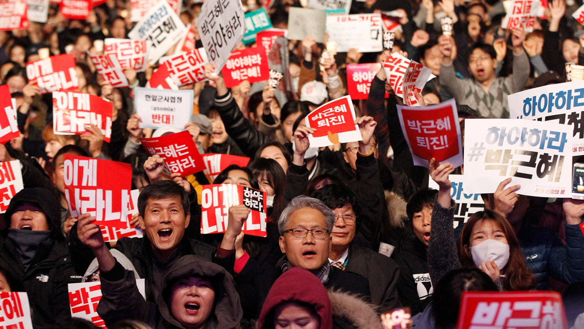 """Nov. 5, 2016: Protesters shout slogans during a rally calling for South Korean President Park Geun-hye to step down in downtown Seoul, South Korea.  The signs read """"Park Geun-hye should step down."""""""