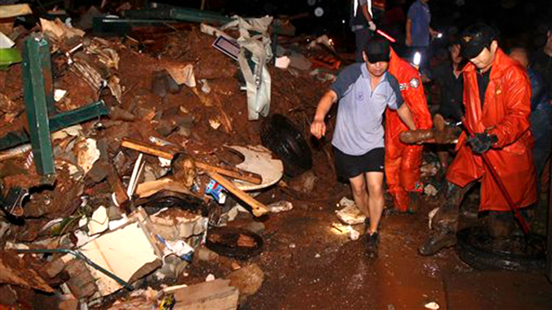 South Korean rescue workers carry a survivor who was rescued from a collapsed house as a midnight landslide caused by torrential rains swept away several houses in Chuncheon, South Korea, Wednesday, July 27, 2011.