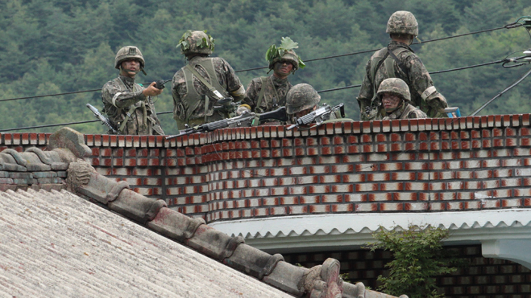 June 22, 2014: South Korean army soldiers take position on the roof of a private house to search for a South Korean conscript soldier who is on the run after a shooting incident in Goseong, South Korea. (AP)