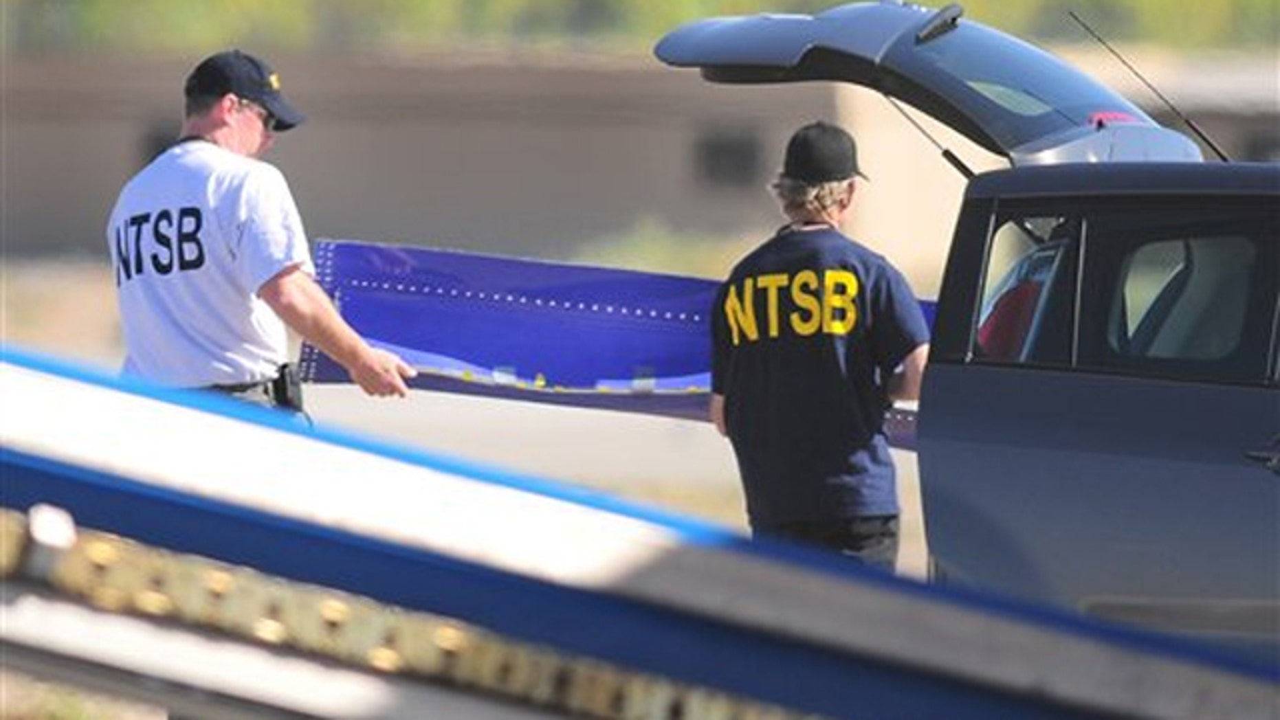 Members of the National Transportation and Safety Board investigating the emergency landing of Southwest Airlines flight 812, carry a portion of the planes fuselage to a waiting vehicle on April 3 in Yuma, Ariz.