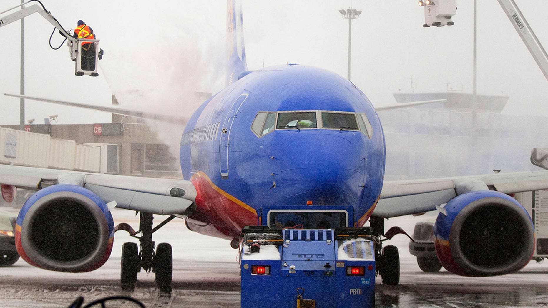 Southwest Airlines crew members are seen de-icing an aircraft at Boston's Logan International Airport in 2014. The airline recently confirmed that a lack of de-icing fluid was responsible for flight cancellations in Chicago on Sunday.